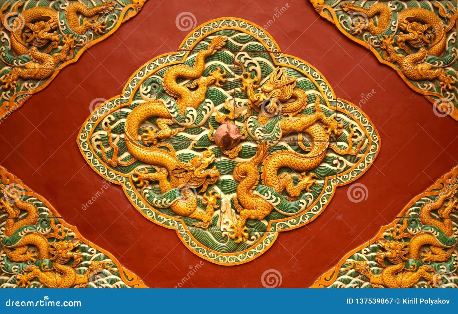 Lövsågsarbete i form av en drake på den röda väggen i Forbiddenet City Peking,