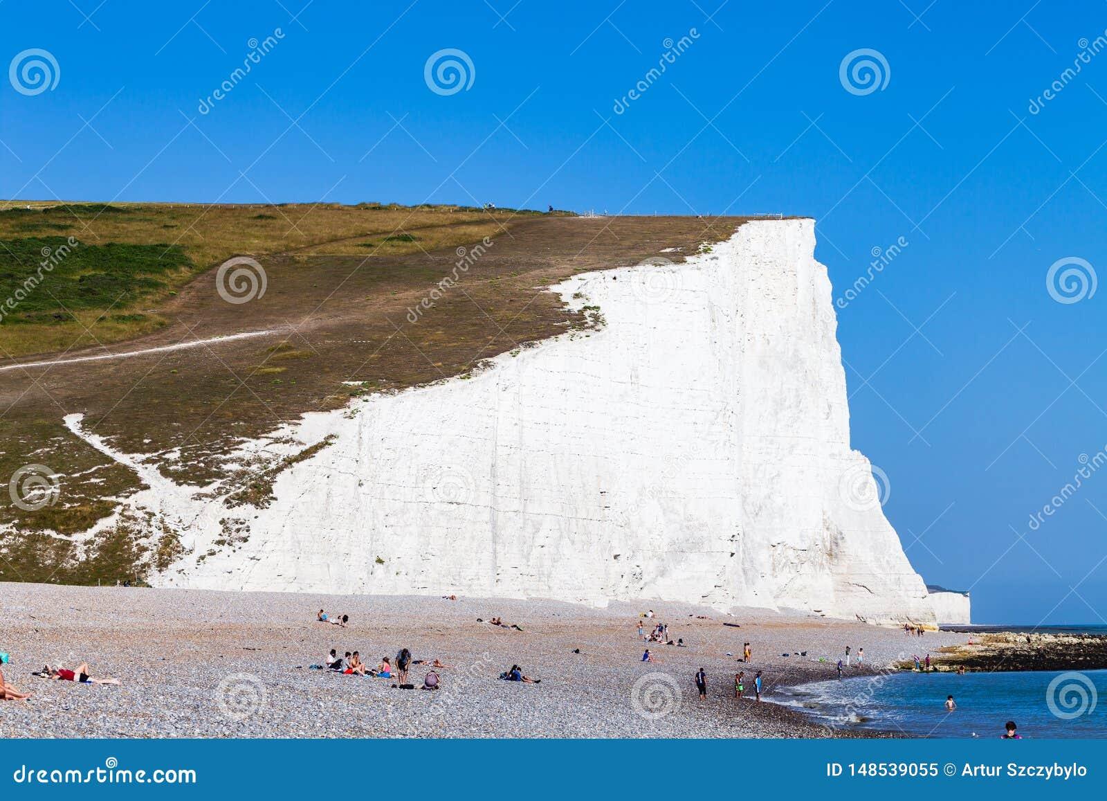 L?genklares Meer des strandes der Vorderansichtstrandklippenleutepersonen sonniger Tages Sommerferienerholung haben Das Gl?nzen w