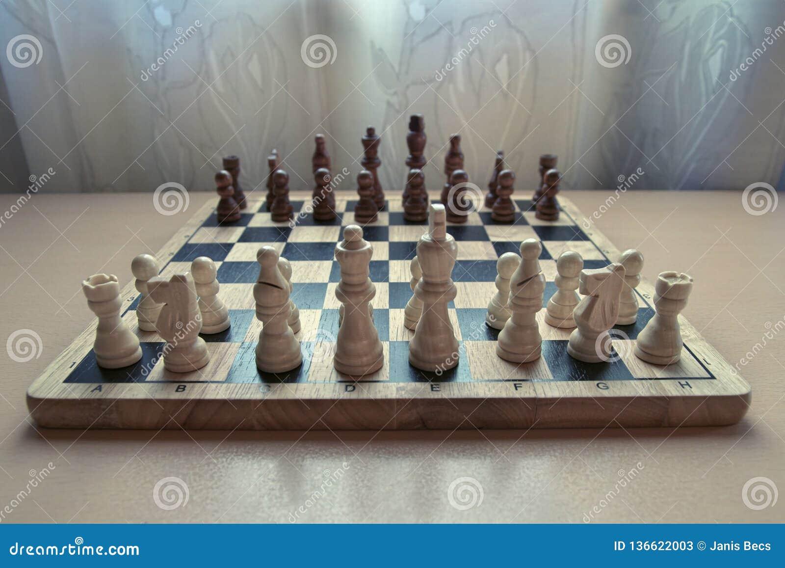 L échiquier matériel en bois de rétro style avec des pièces d échecs a placé prêt pour le jeu d esprit stratégique