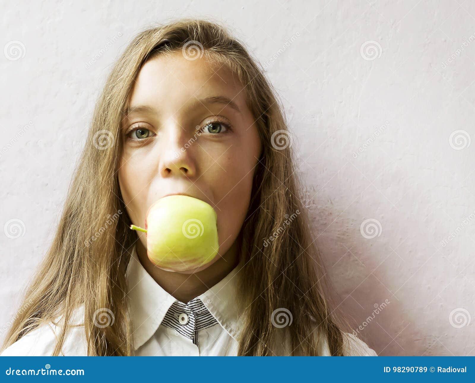 L écolière blonde mignonne de fille mord une pomme verte Nourriture saine
