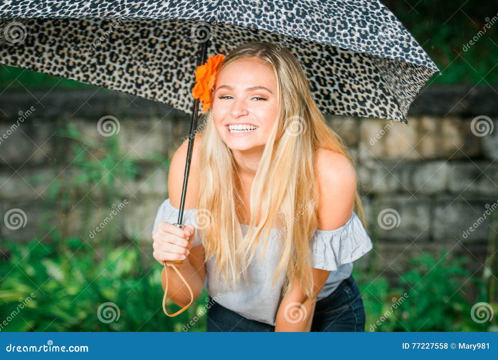 L élève de terminale pose avec le parapluie pour des portraits sur un pluvieux