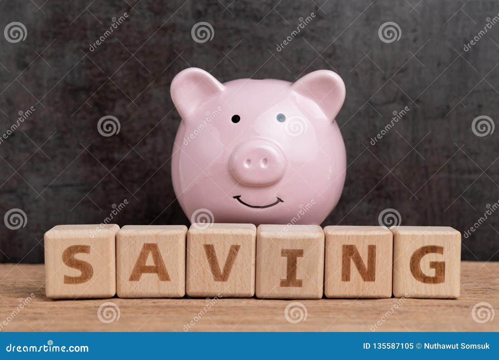 L épargne heureuse, budget, investissement ou buts financiers concept, tirelire de rose de sourire et pile de mot en bois de bâti