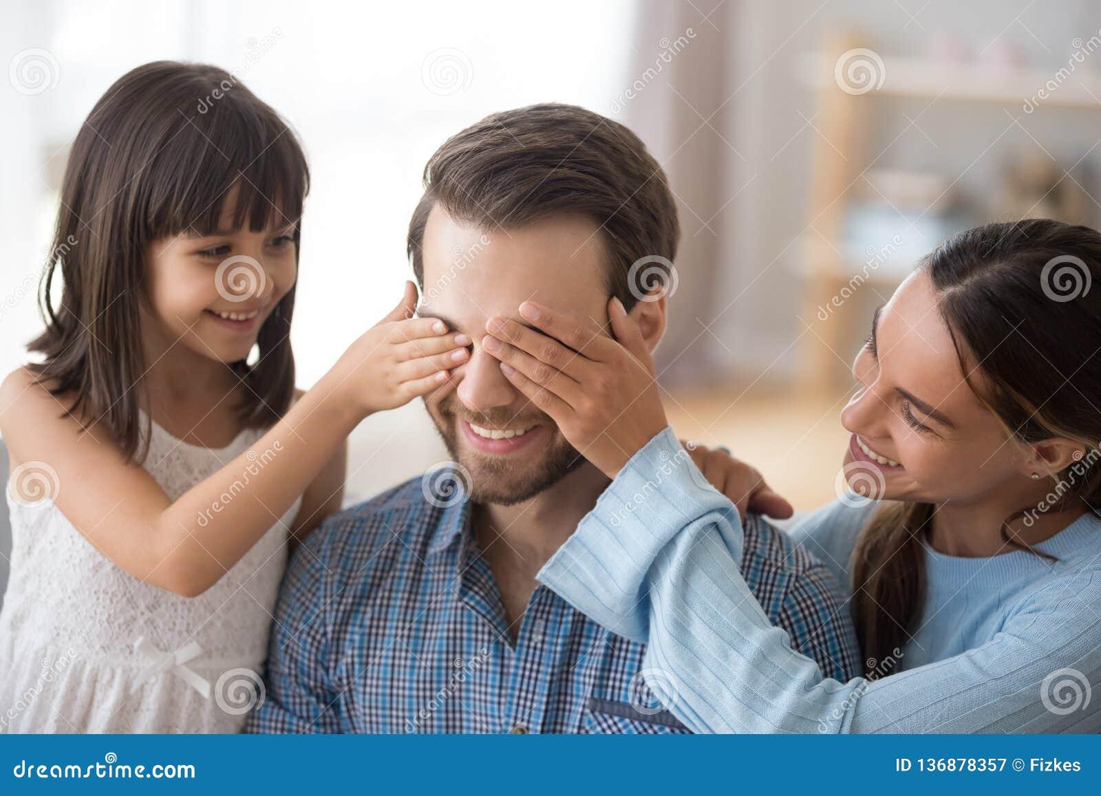 L épouse avec les yeux se fermants d enfant du papa de sourire font la surprise