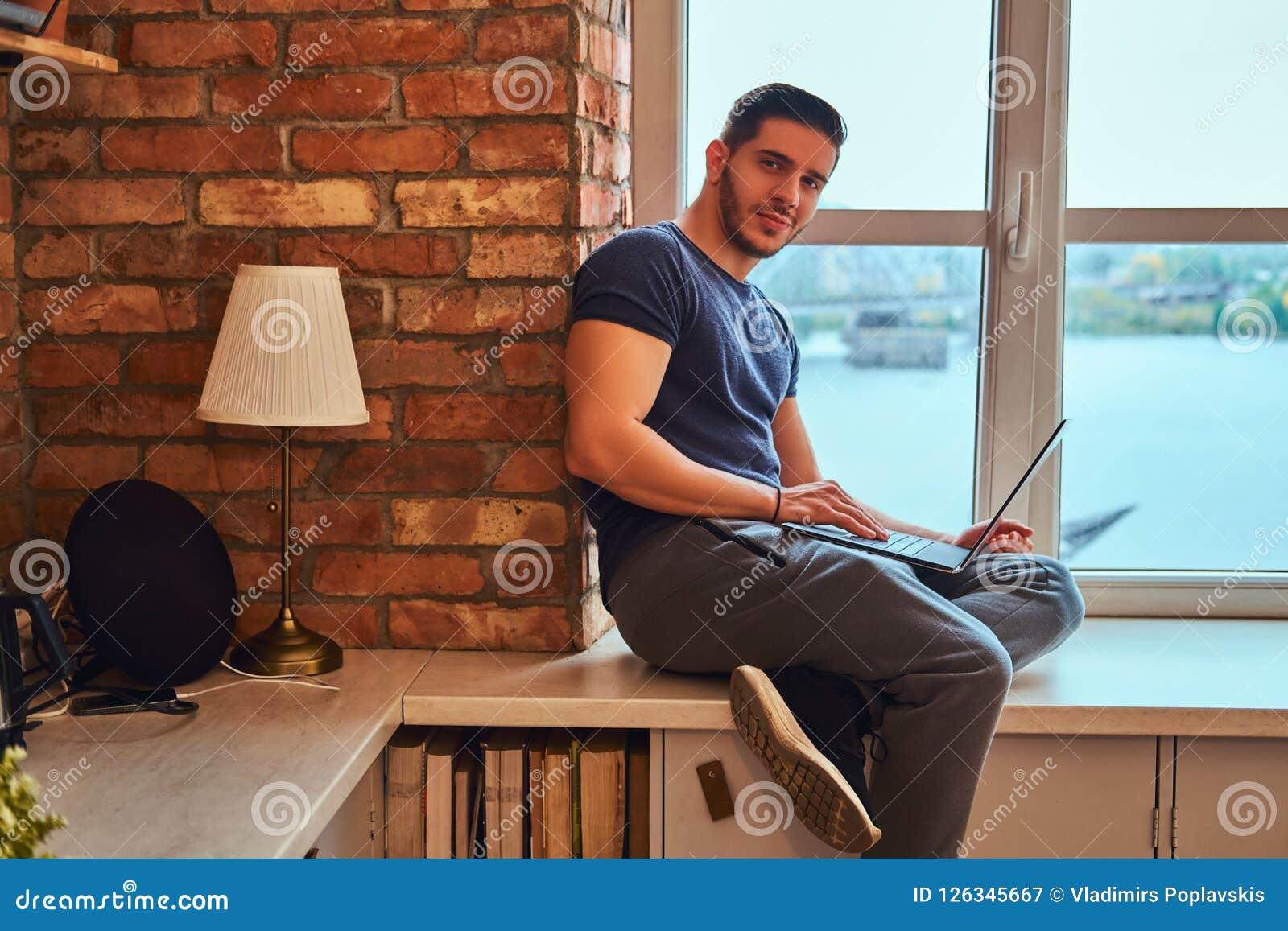 L étudiant grec bel tient l ordinateur portable tout en se reposant sur un filon-couche de fenêtre dans le dortoir d étudiant