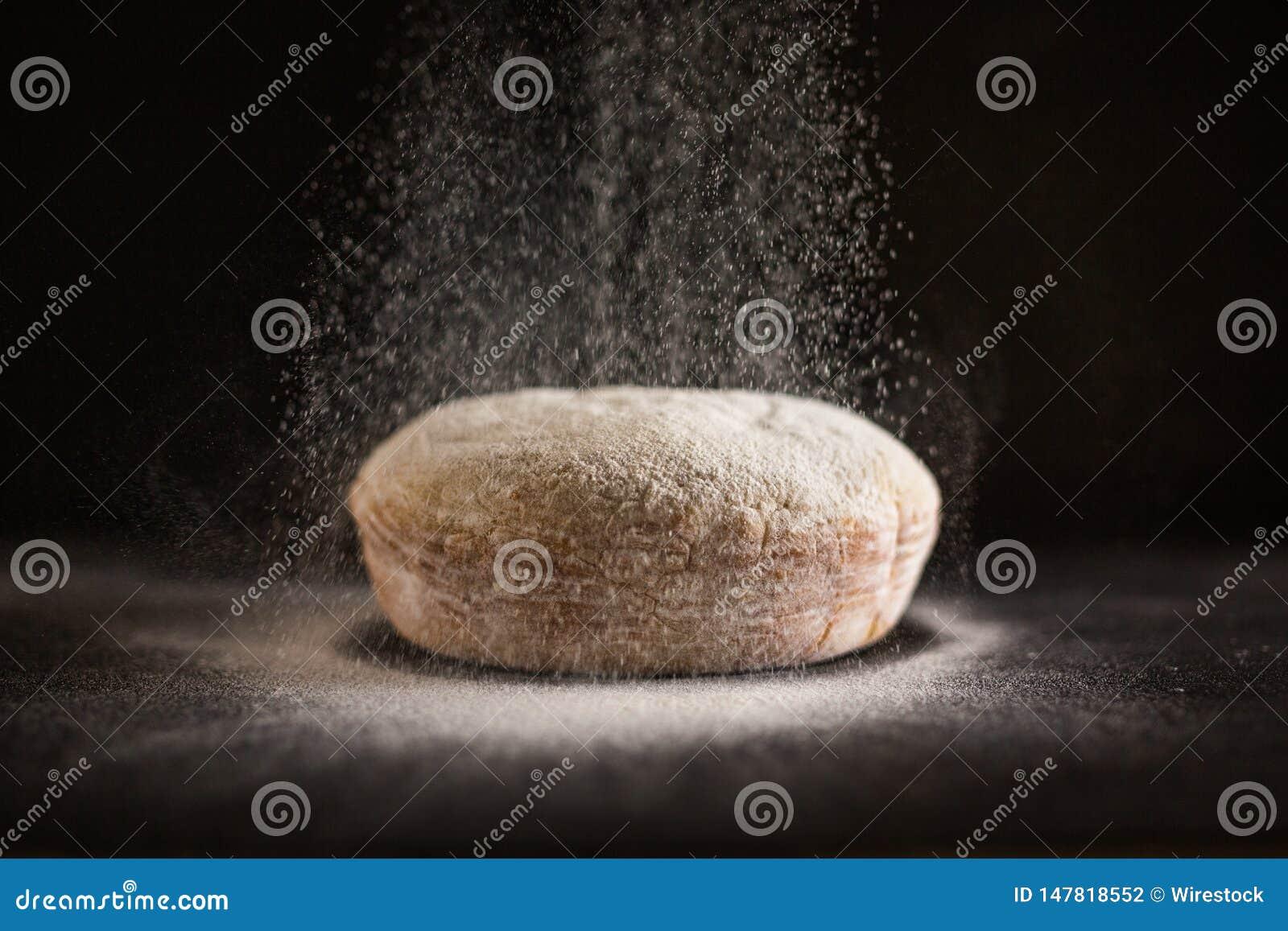 L être de farine a arrosé sur le pain cuit au four frais