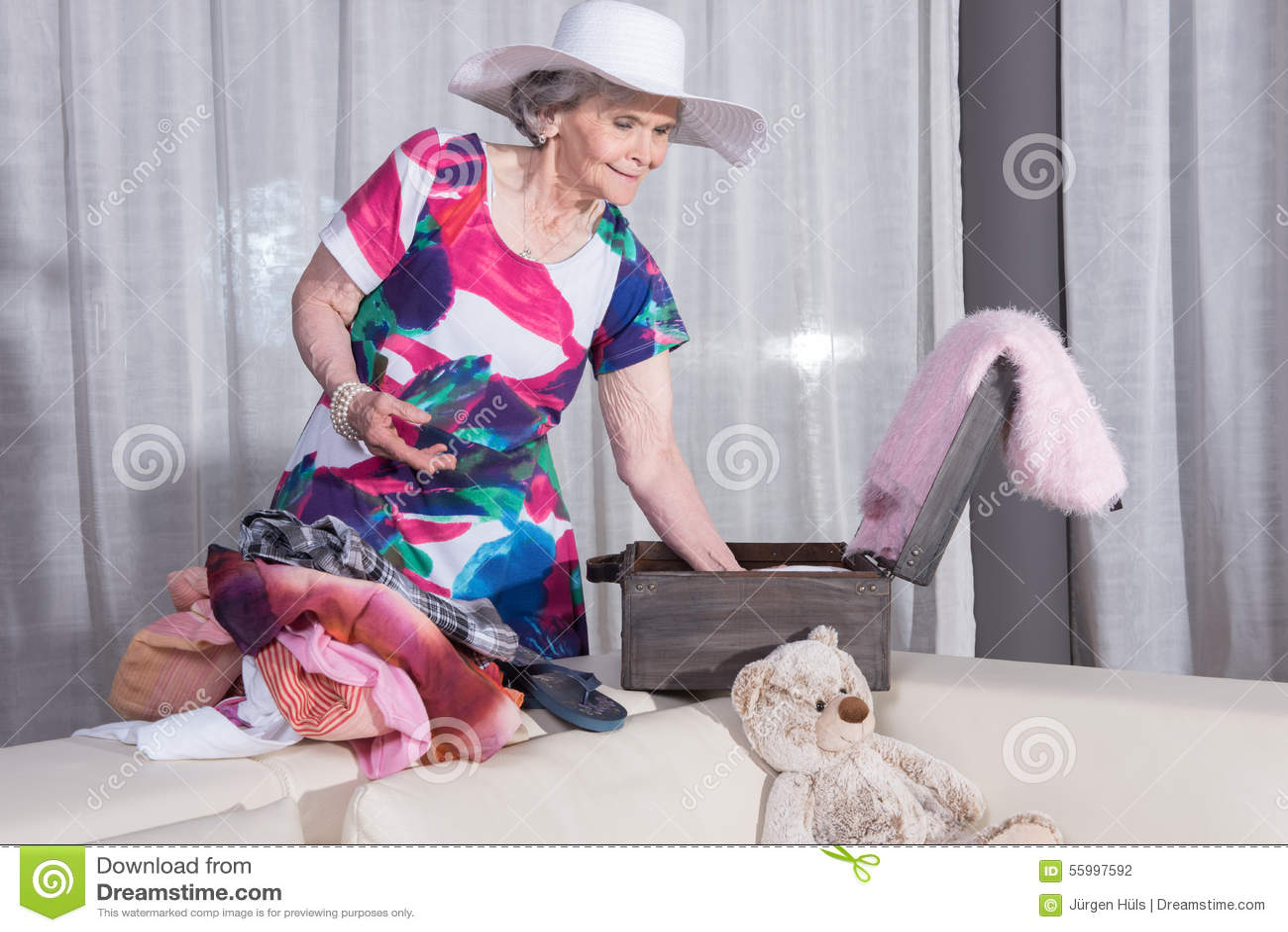 L aîné féminin actif emballe la valise de vintage pour des vacances d été