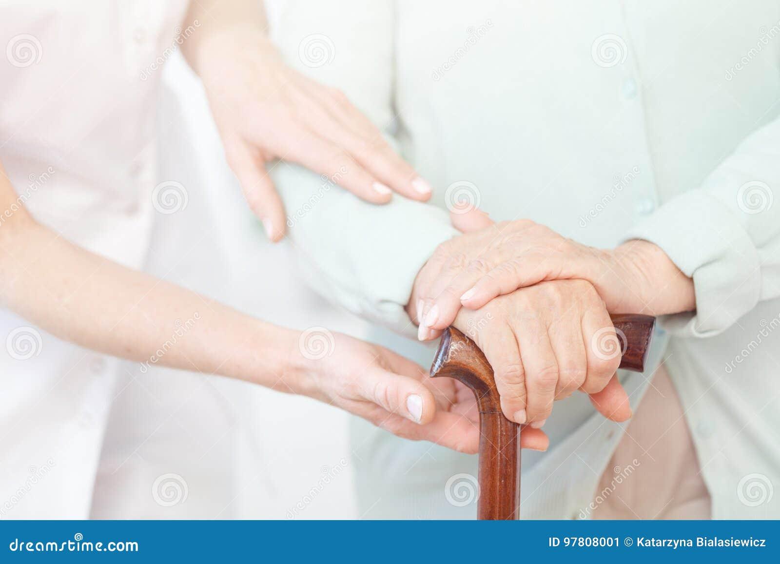 L aîné tient des mains sur le bâton de marche