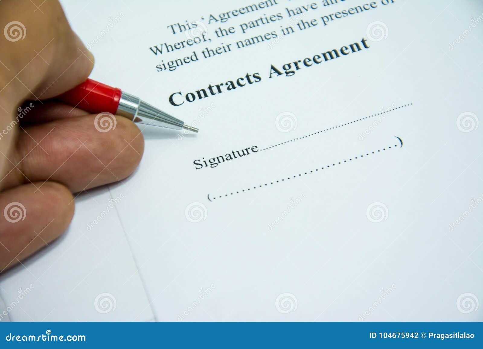 L accord de contrats se connectent le papier de document avec le stylo rouge