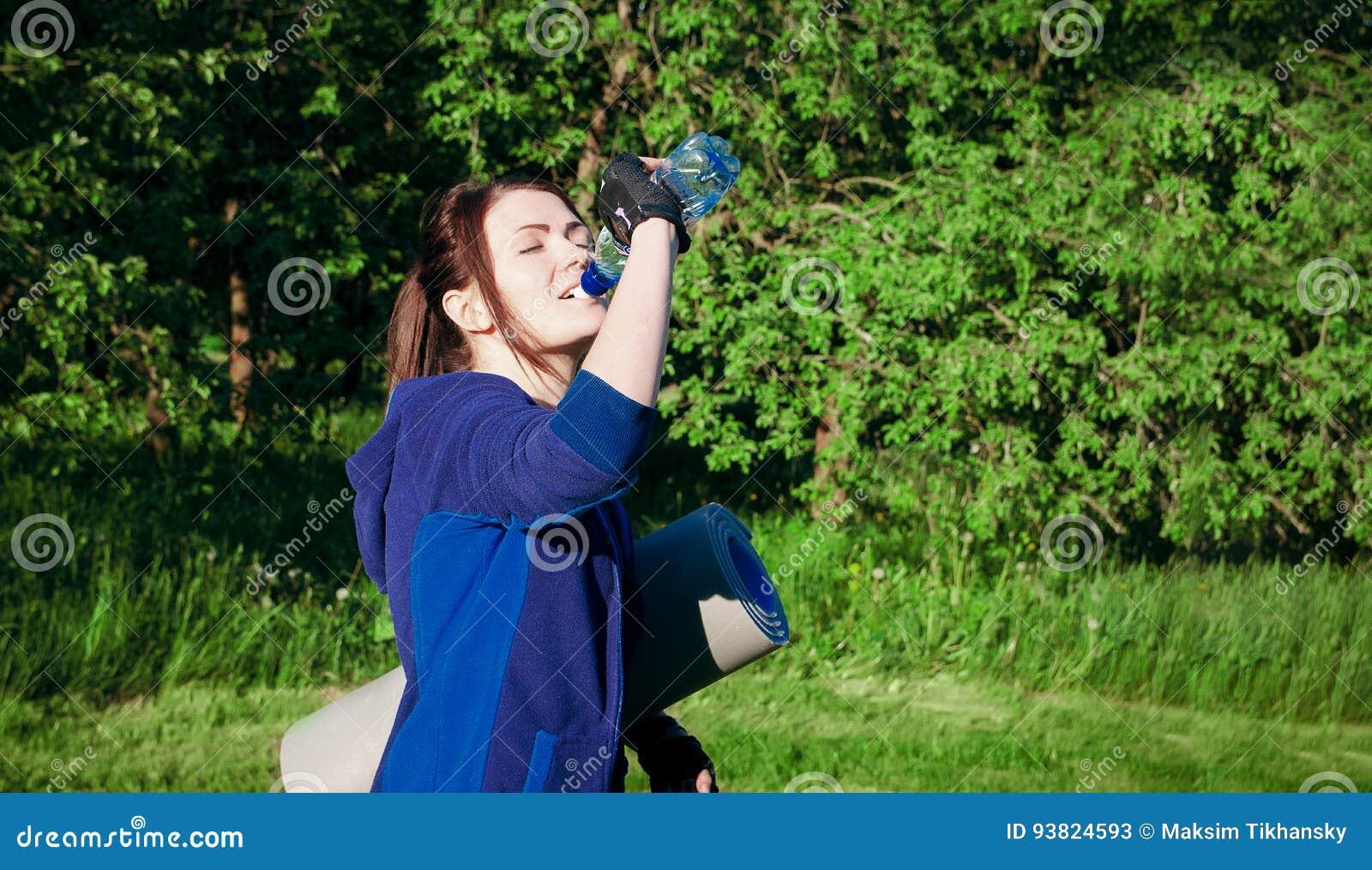 L acqua della bevanda della ragazza durante l allenamento