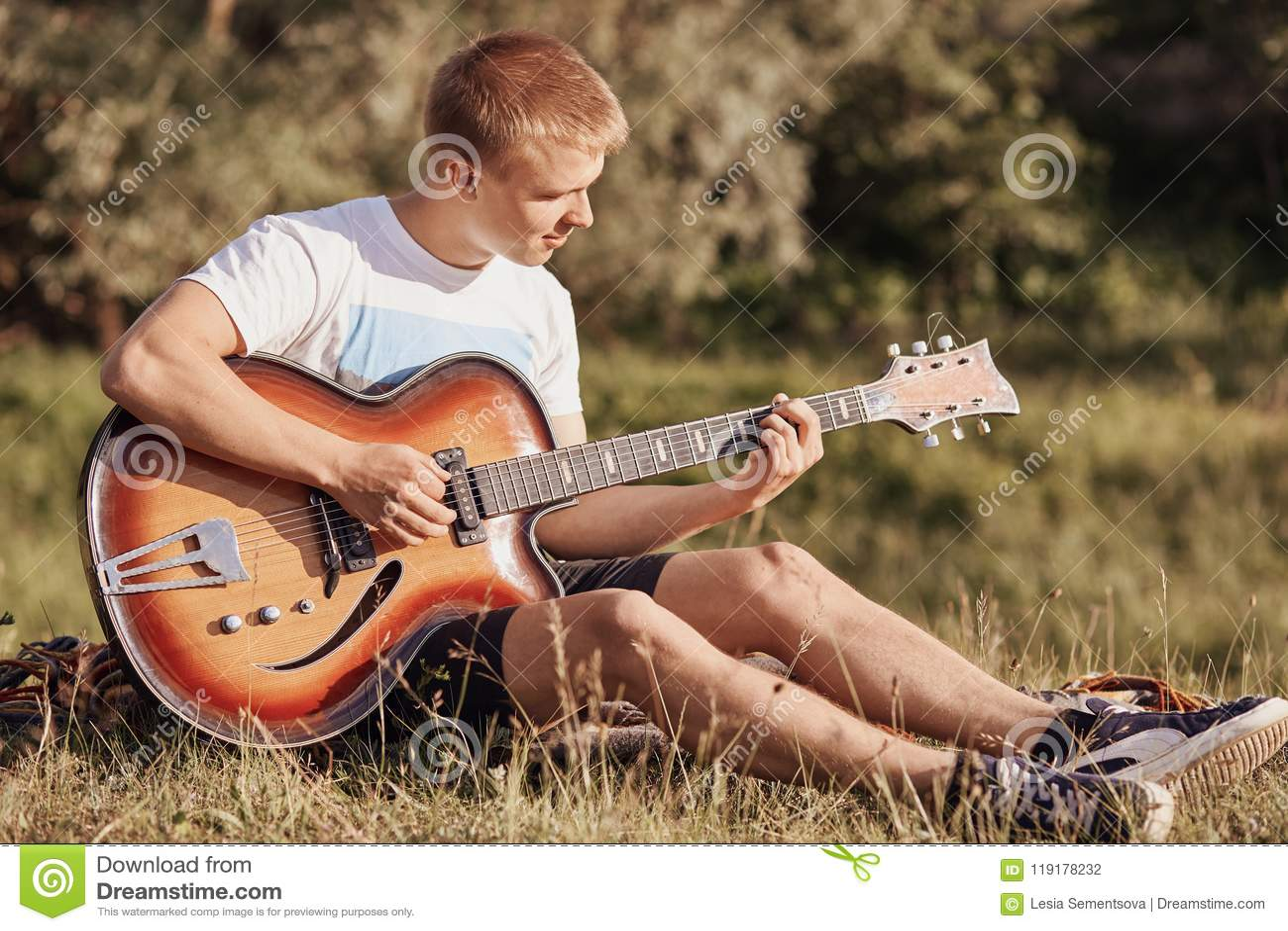 L adolescent masculin européen attirant s assied sur l herbe, joue la guitare acoustique, recreats pendant le jour d été, nouvell
