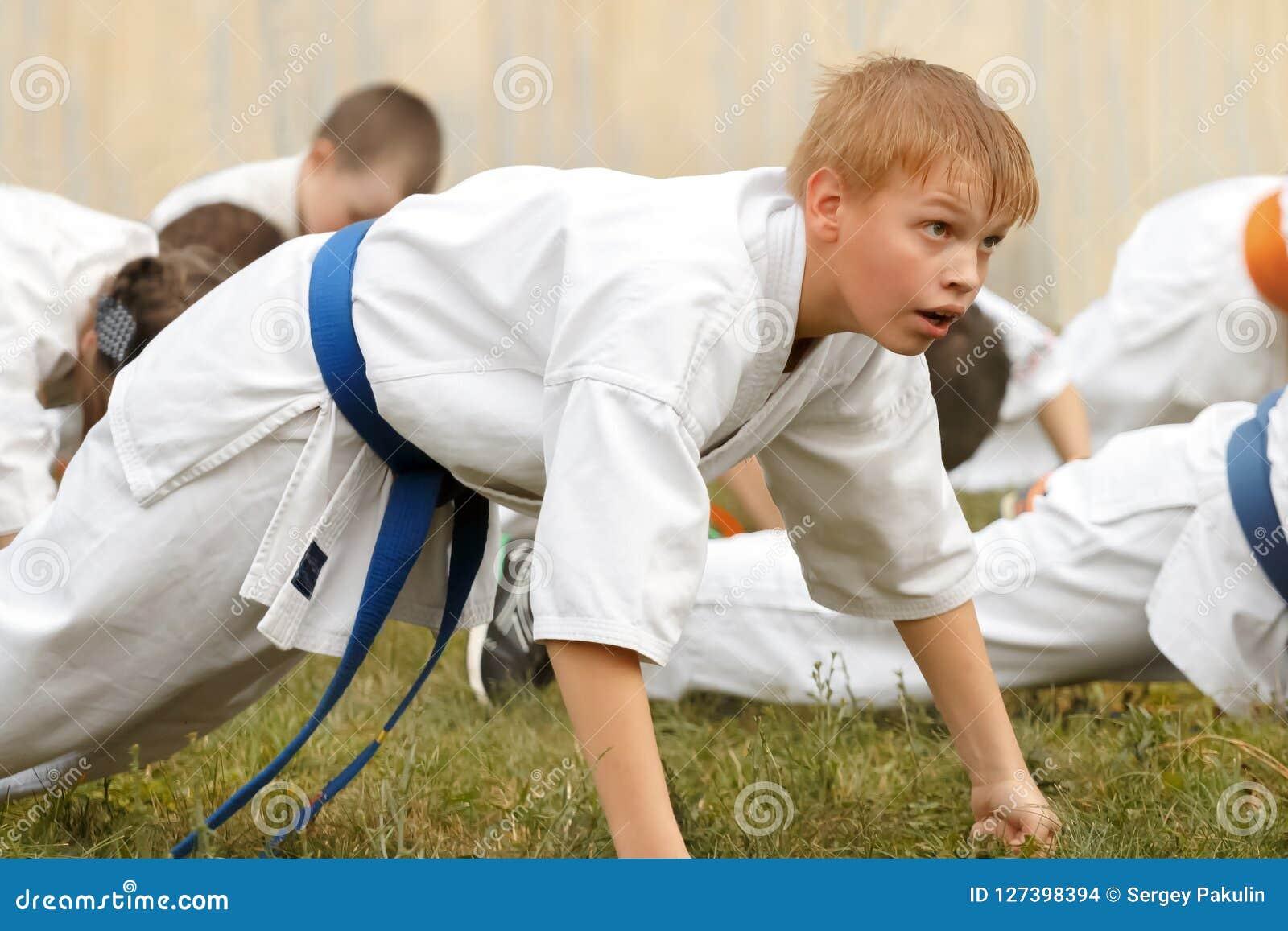 L adolescente del ragazzo in kimono esegue spinta-UPS sui pugni