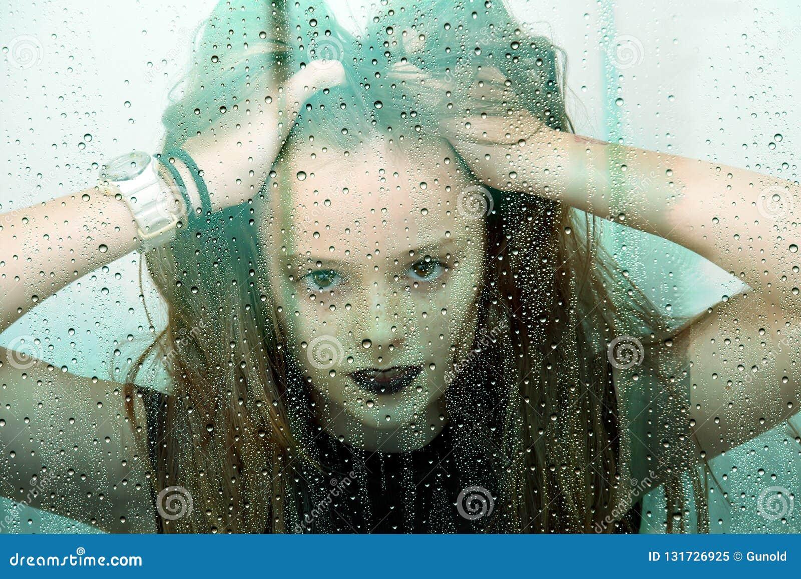 L adolescente derrière la fenêtre avec des gouttes de pluie ébouriffe ses cheveux