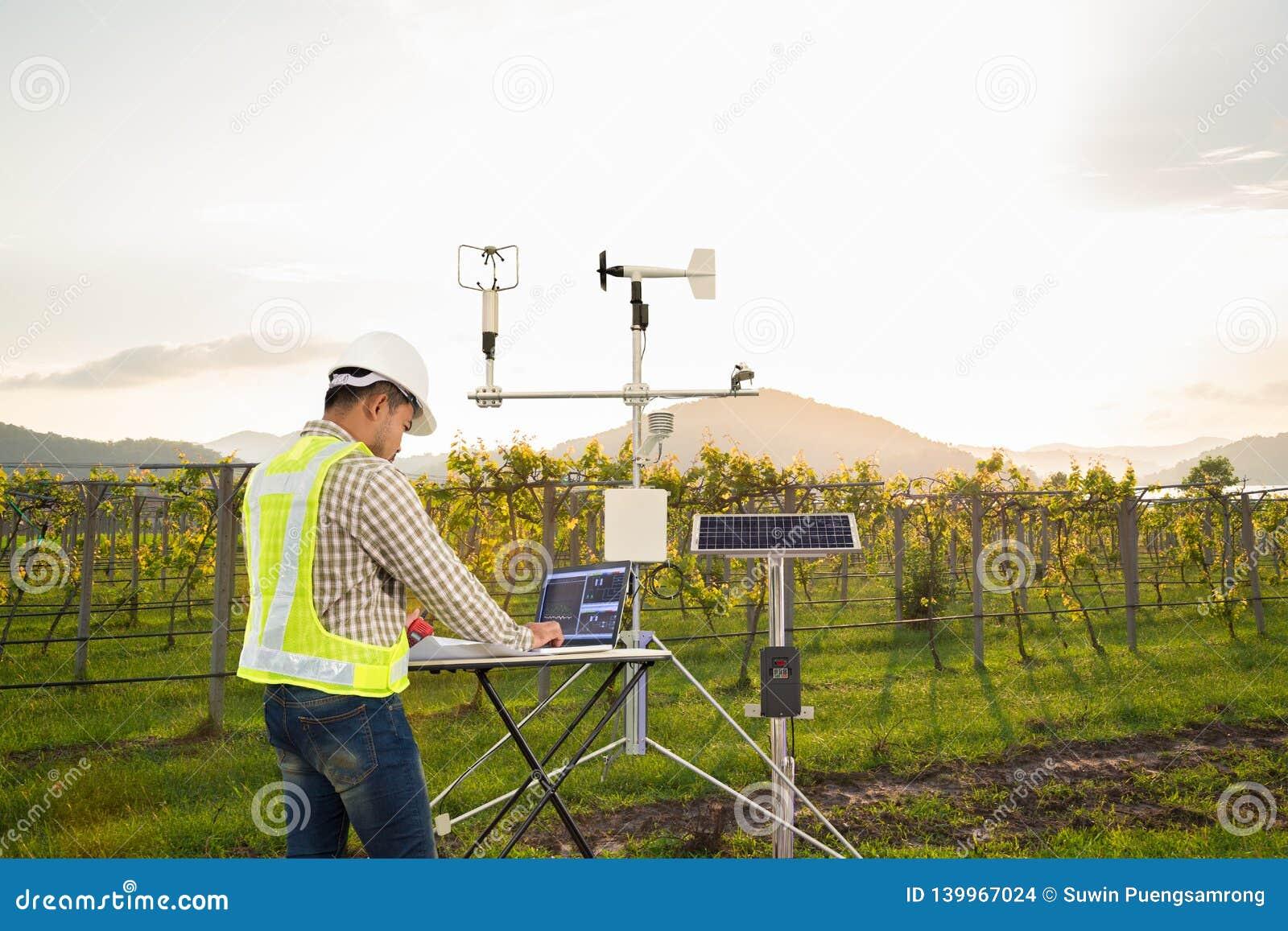 L agronomo che per mezzo del computer della compressa raccoglie i dati con lo strumento meteorologico per misurare la velocità de