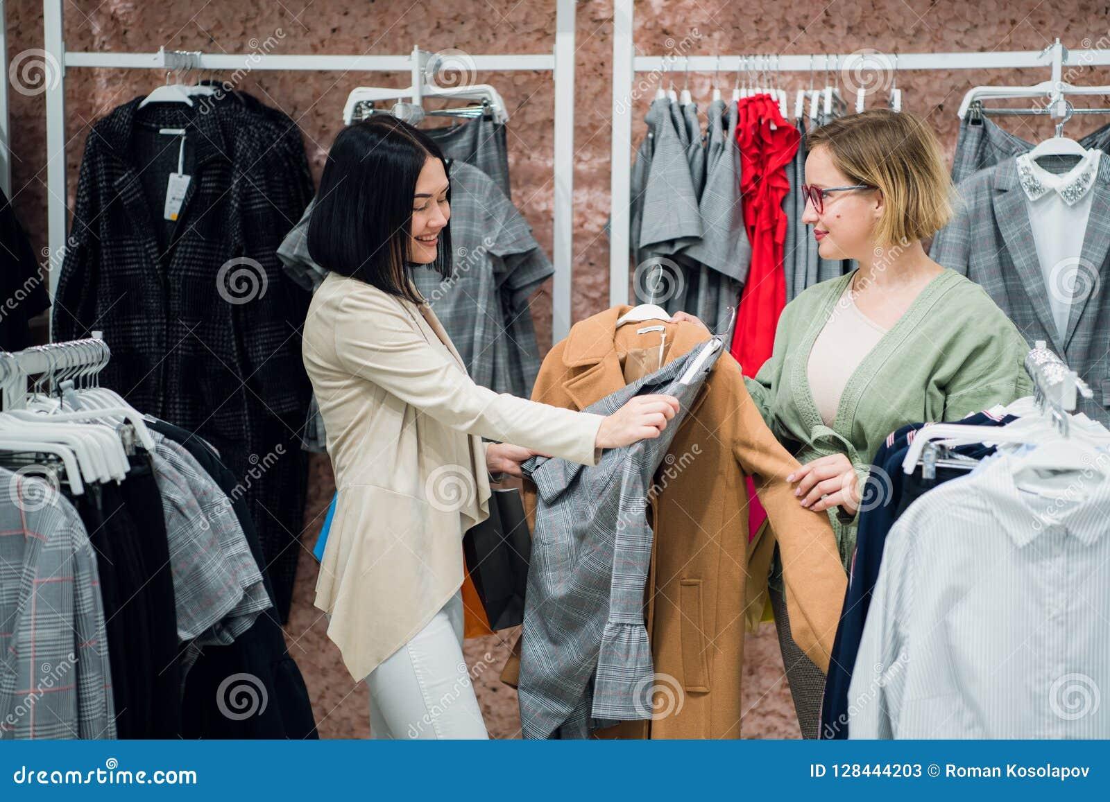 L aide de consultant en matière de ventes choisit des vêtements pour le client dans le magasin Achat avec le concept de styliste