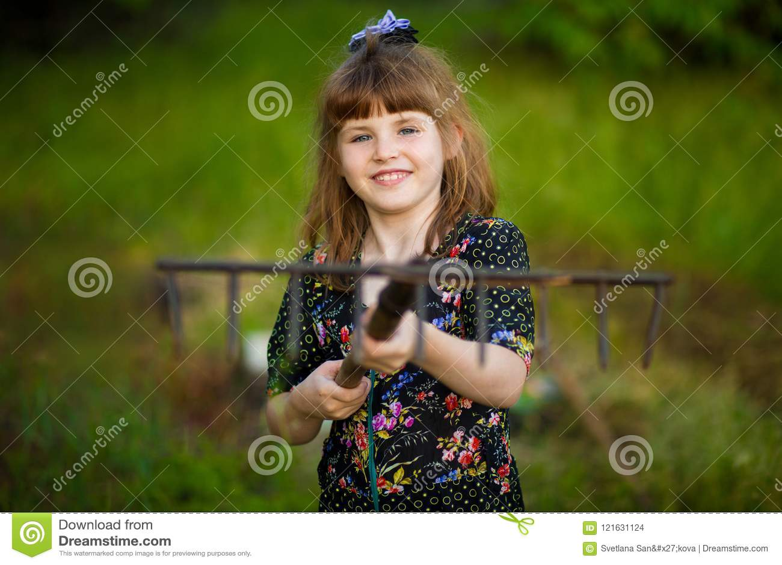 L aide heureuse de petite fille parents dans le jardin avec le râteau