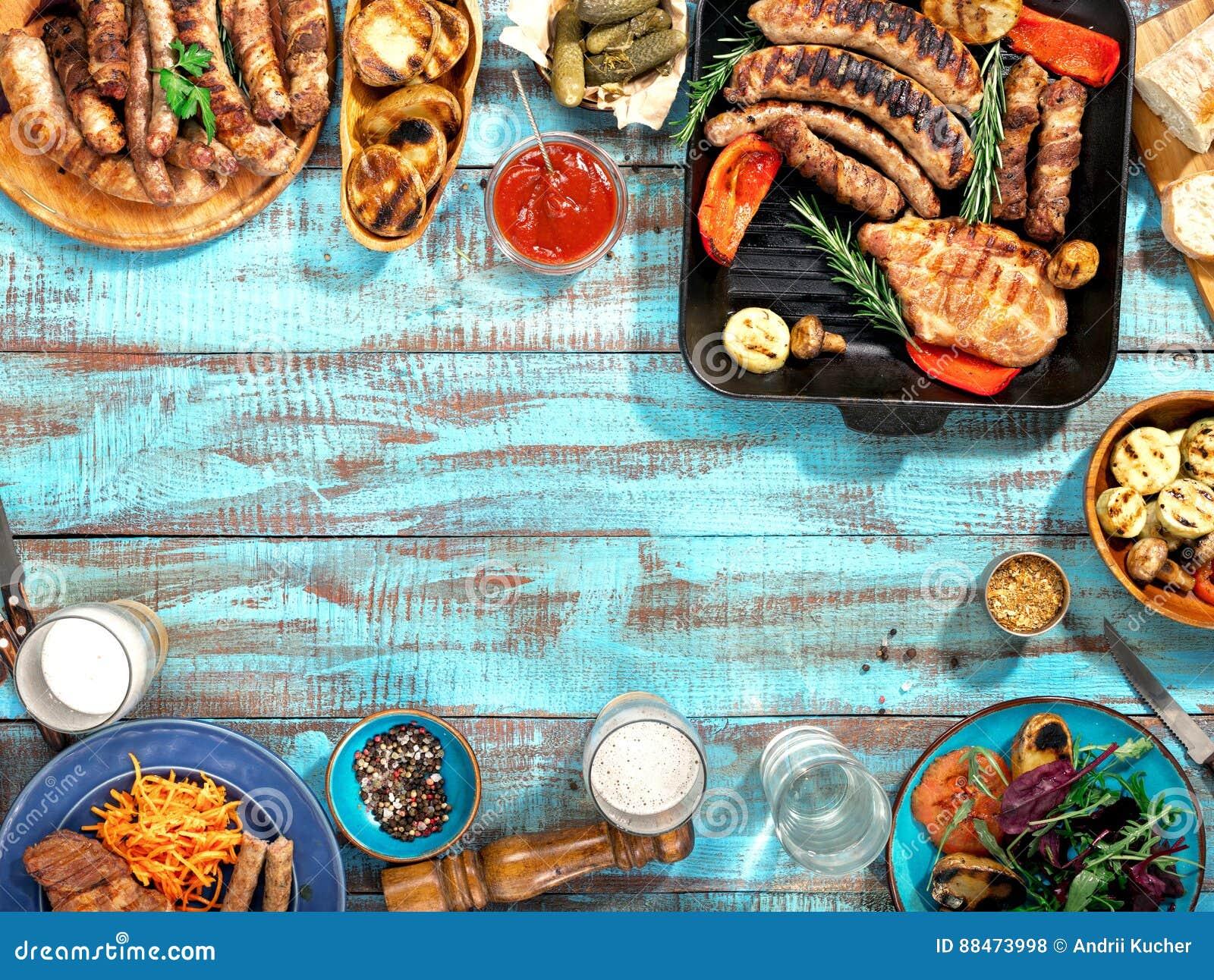 L alimento differente ha cucinato sulla griglia sulla tavola di legno blu