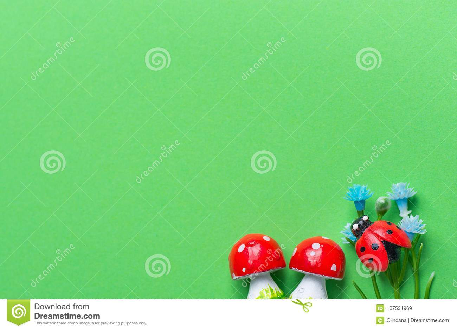 L amanita si espande rapidamente fiori Ladybird del blu di Smal sulla pianta verde dell erba di imitazione del fondo Composizione