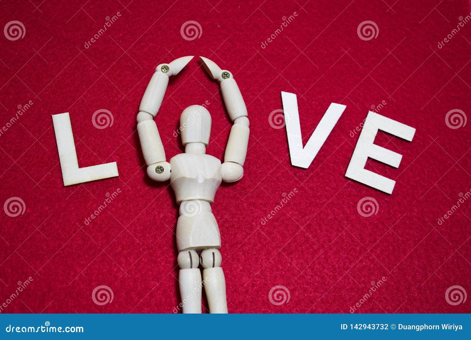 L amour les lettres qu en bois avec la marionnette en bois fanent dessus l acrylique de couleur s est senti