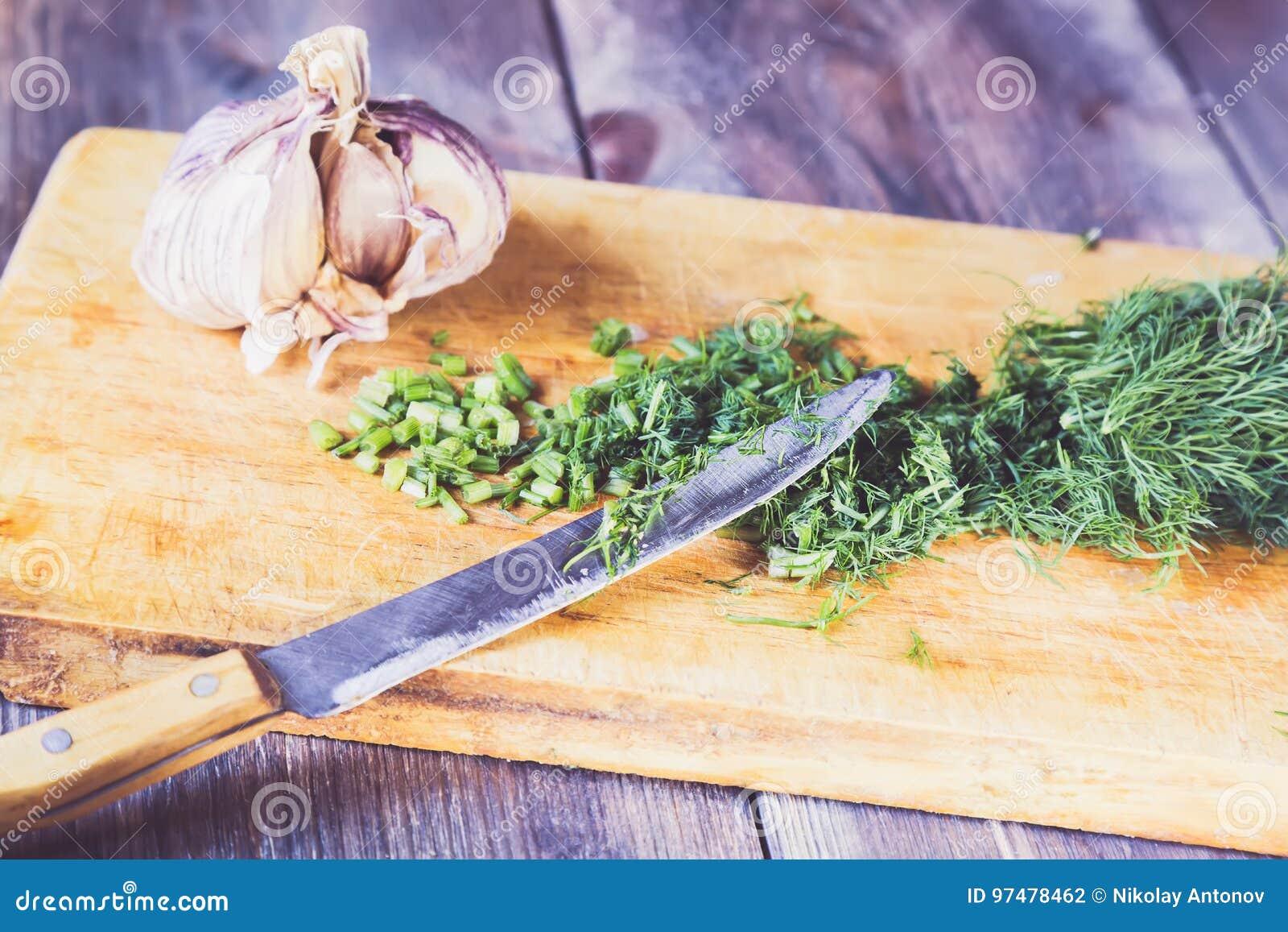 L aneto verde fresco ha tagliato sul tagliere della cucina con un coltello e garnic sulla tavola di legno
