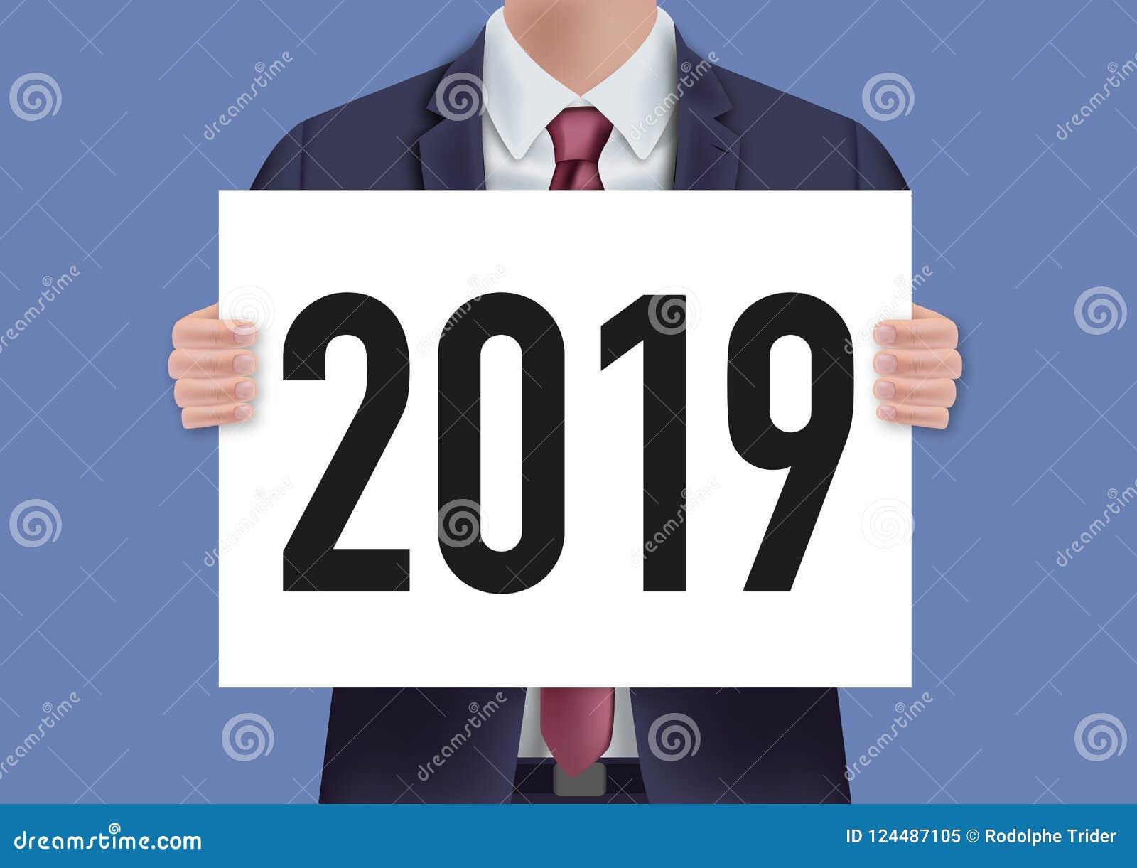 L année 2019 inscrite sur un panneau blanc s est tenue par un homme dans un costume