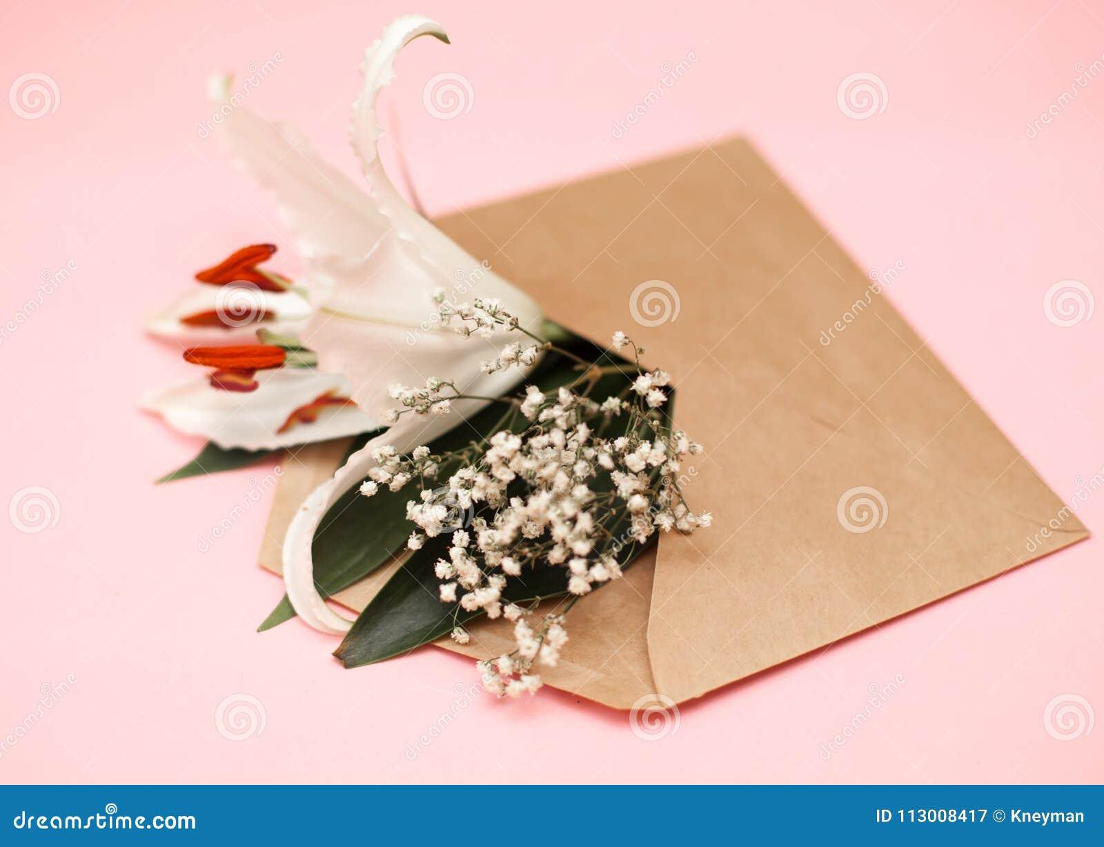 L appartement décoratif étendent la composition avec l enveloppe et les fleurs de papier d emballage Configuration plate, vue sup