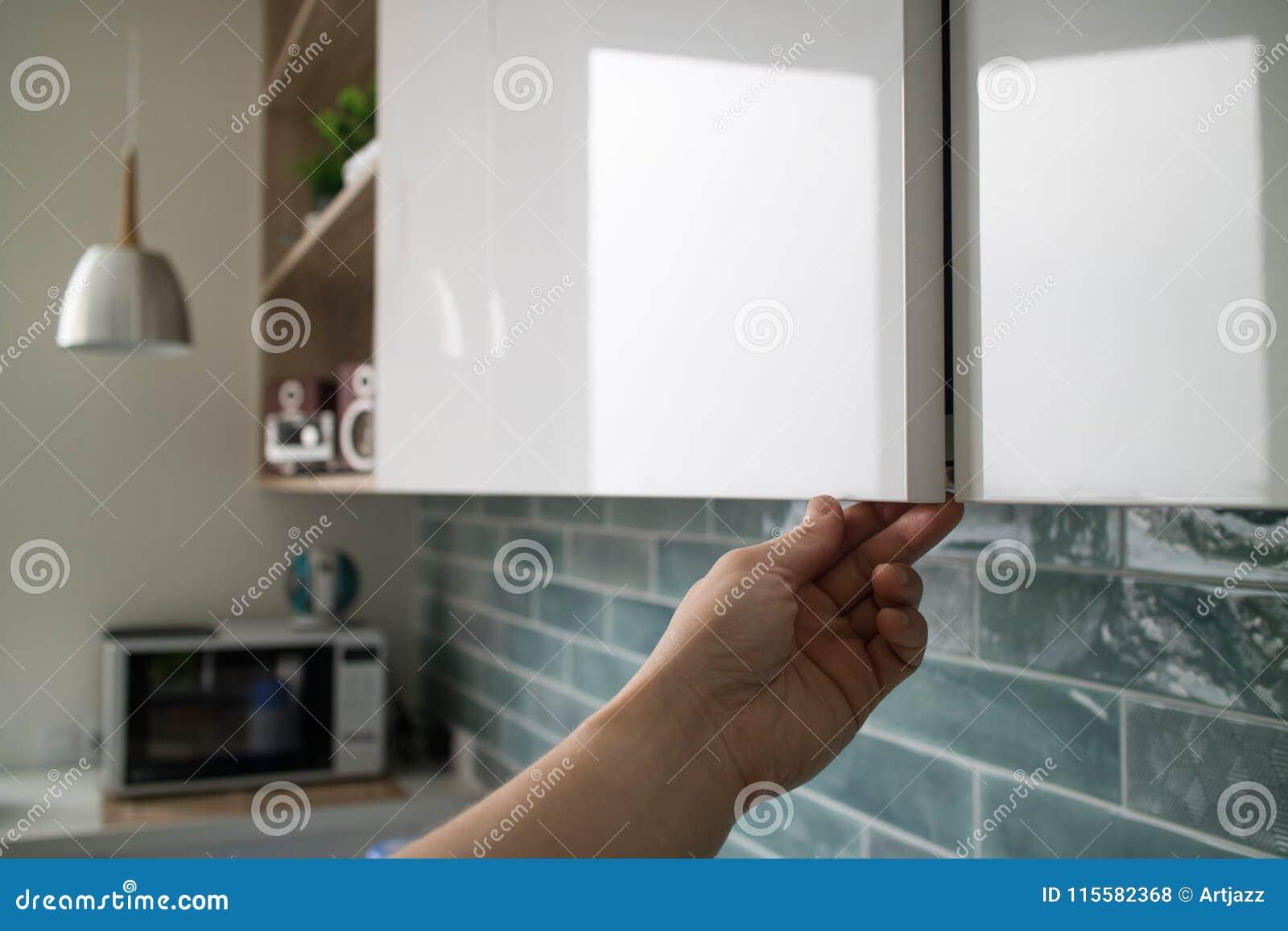L\'armadio Da Cucina Con Le Porte Senza Maniglie, La Mano Del ...