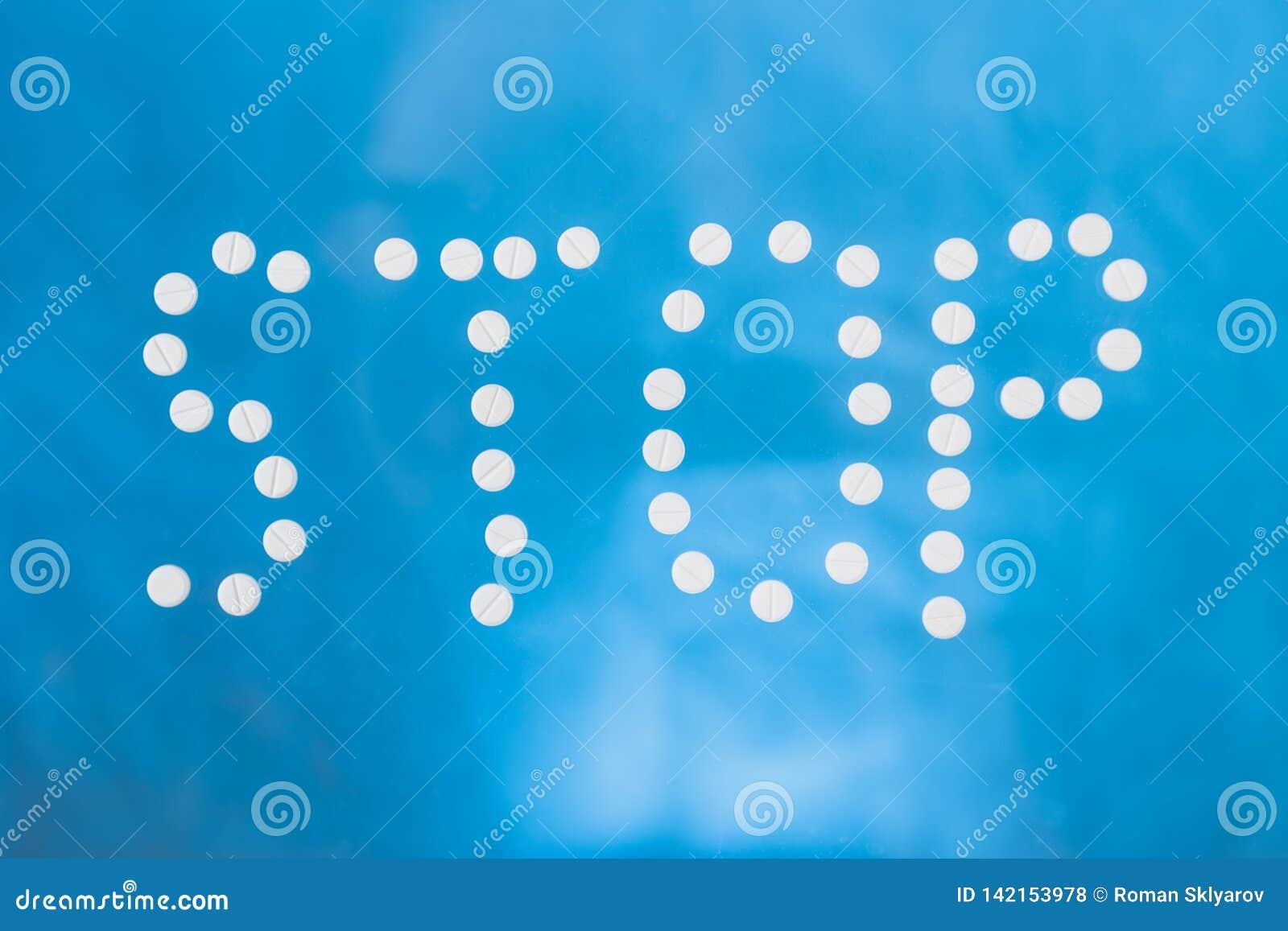 L arrêt d inscription présenté des pilules blanches sur un fond bleu