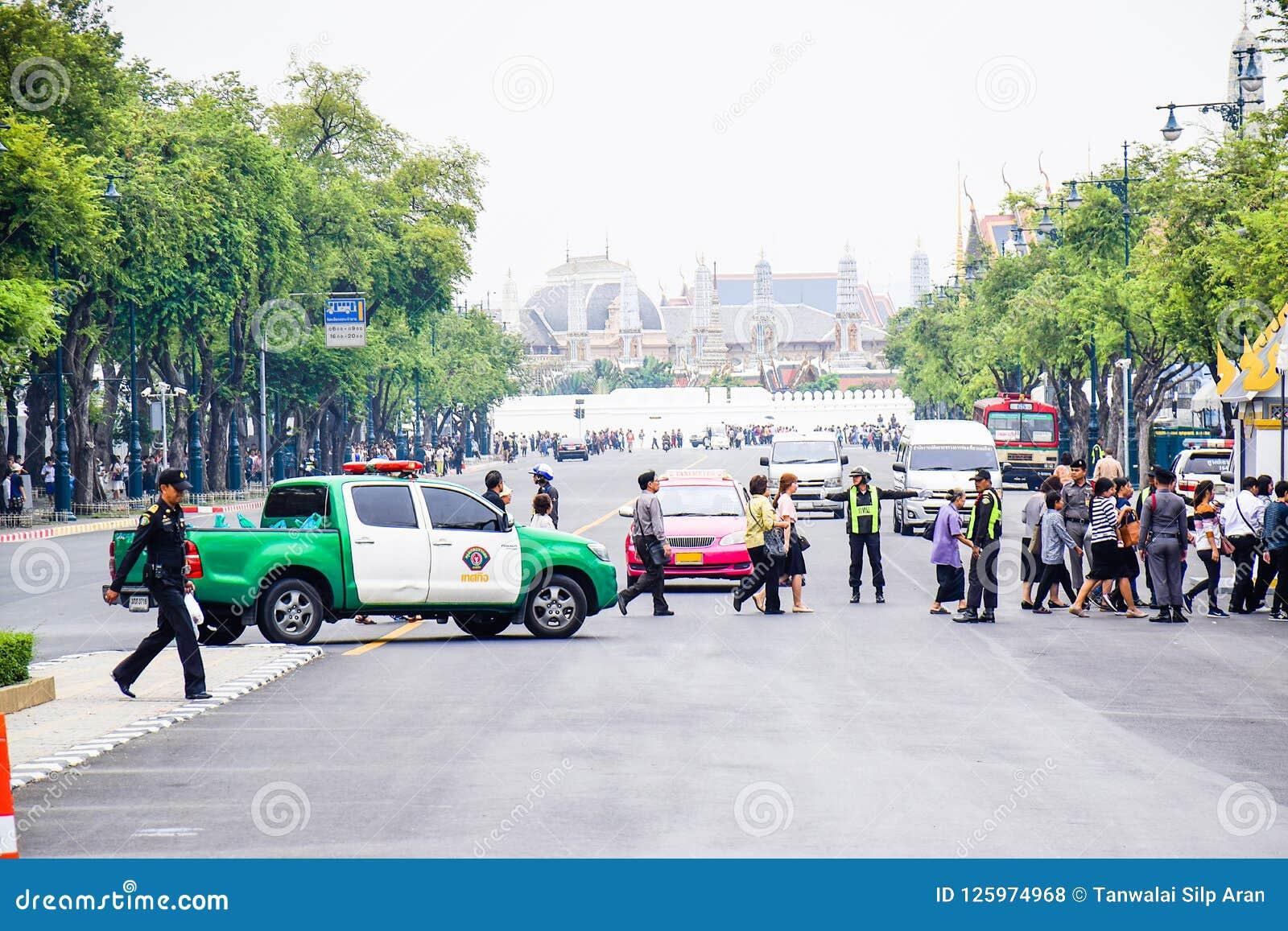 L arrêt de policier les voitures pour des personnes traversant la route vont à Sanam