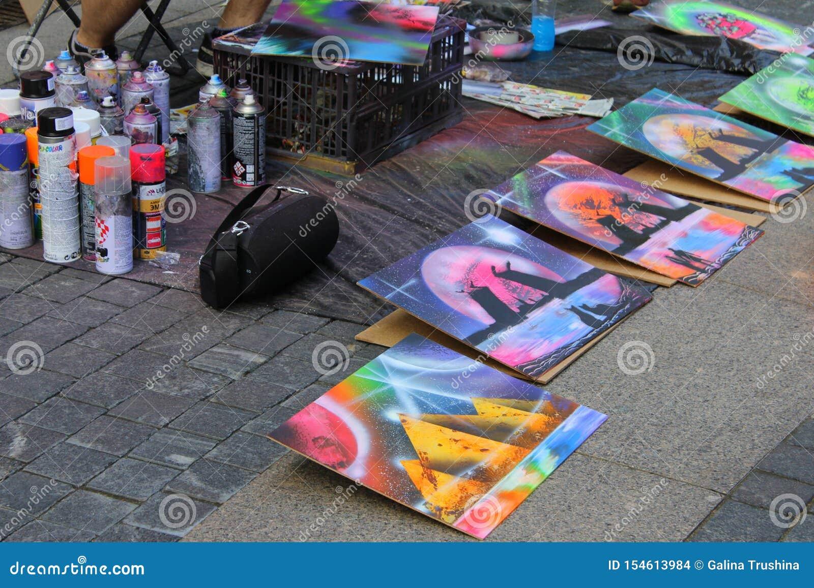 L artista della via dipinge una latta di pittura su carta per i compratori