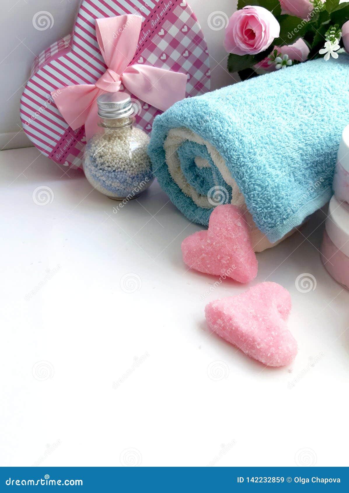 L asciugamano, contenitore di regalo, bottiglia cosmetica, sale sfrega la forma di cuore su fondo bianco