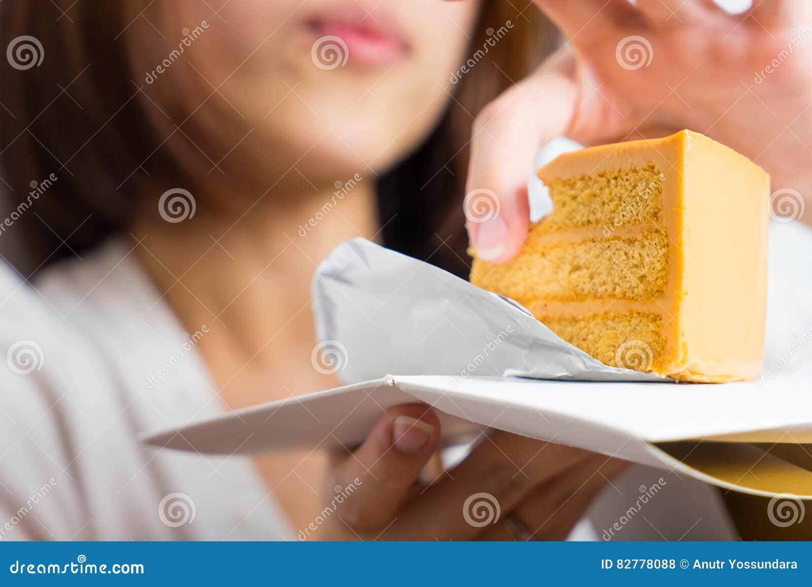 L Asiatique féminin mange le gâteau de caramel avec la main