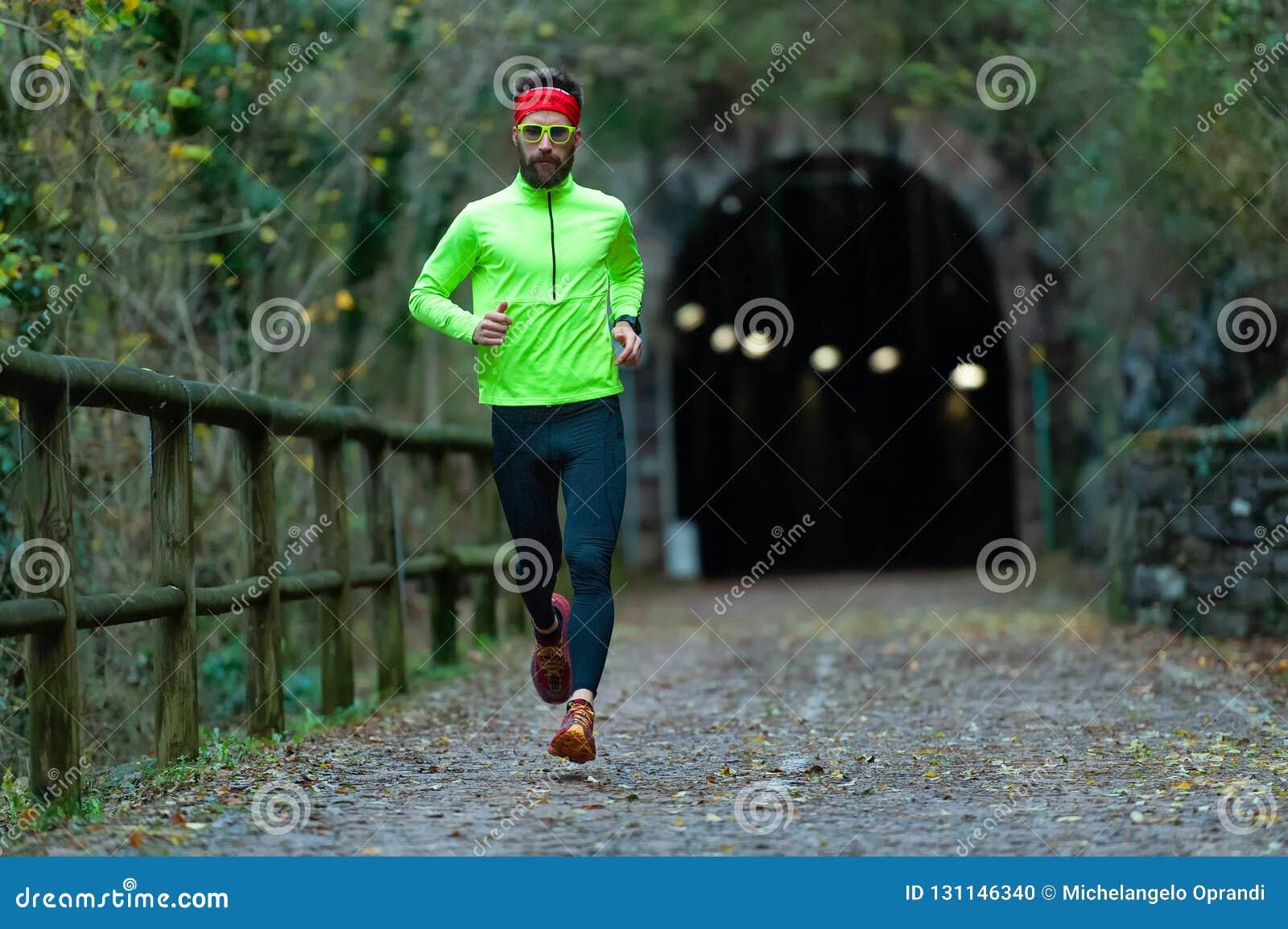 L atleta dell uomo funziona sul percorso della bici fra i tunnel nella caduta