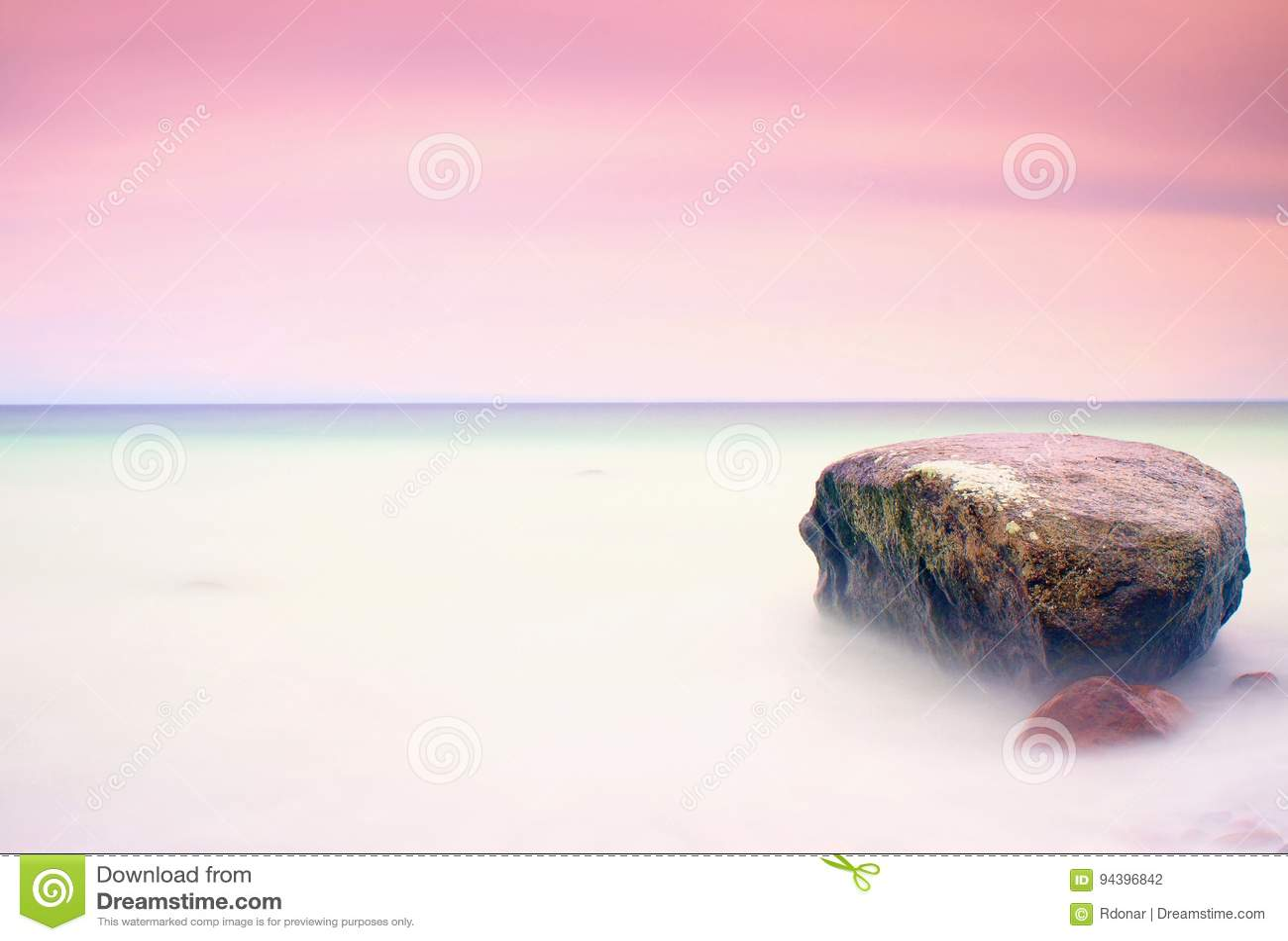 L atmosphère romantique dans le matin paisible en mer Grands rochers collant de la mer onduleuse lisse Horizon rose