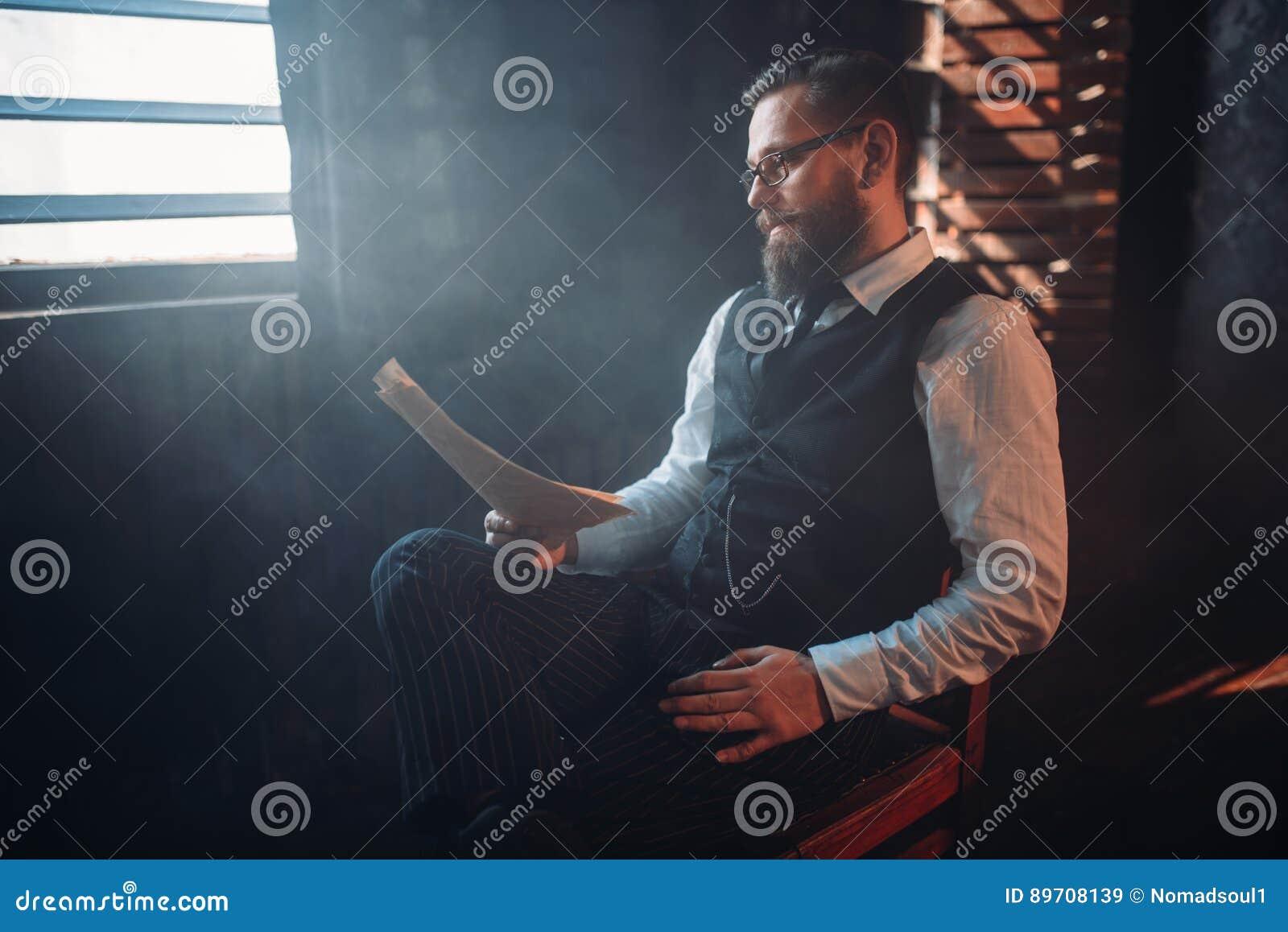 L auteur barbu en verres lit le texte manuscrit
