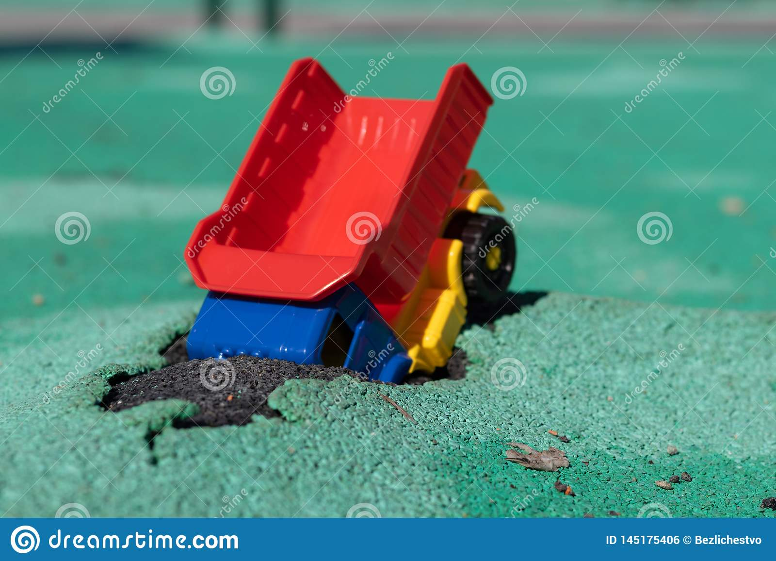 L automobile è caduto nel pozzo Il camion di plastica del giocattolo con un corpo rosso ha avuto un incidente Foro su Asphalt Co