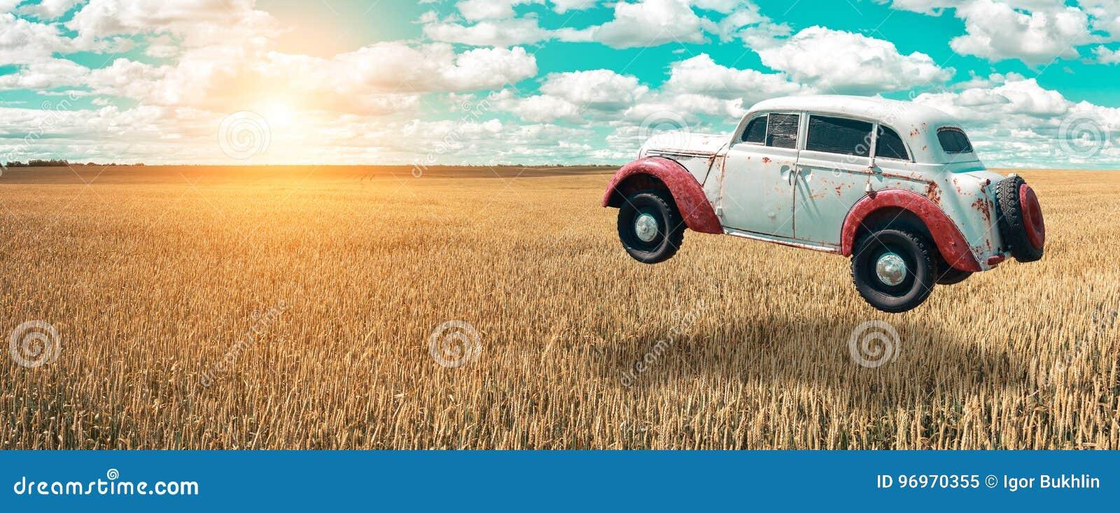 L automobile di volo sale nel cielo La retro automobile si libra nell aria sopra un giacimento di grano dorato sui precedenti di