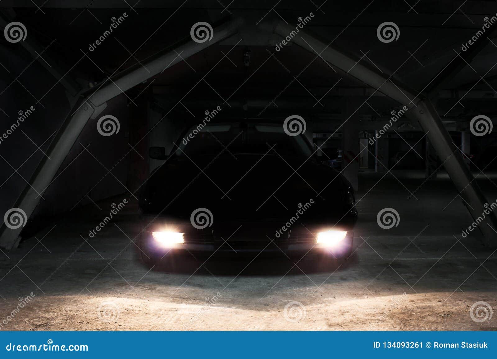 L automobile nelle ombre con le luci d ardore alla scarsa visibilità