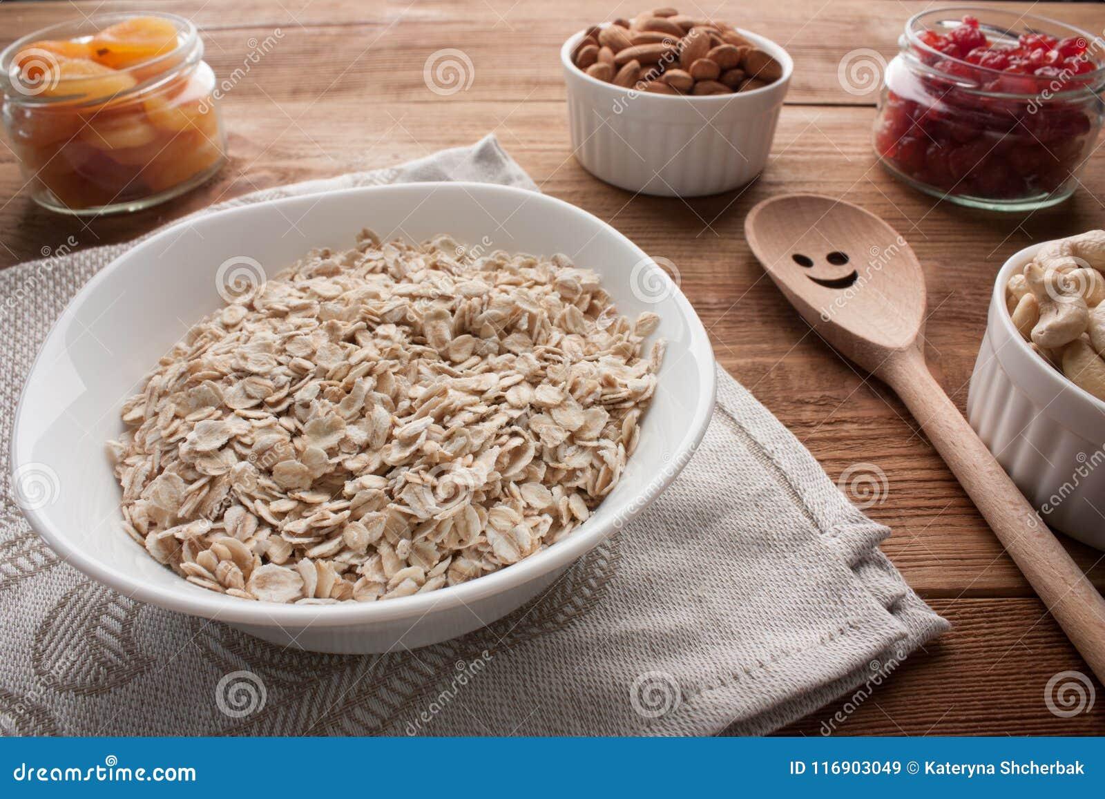 L avena si sfalda in ciotola con le albicocche secche, ciliege secche, mandorle, anacardii in barattoli sulla tavola di legno con