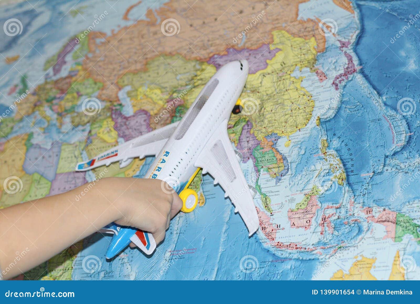 L avion de jouet vole par la carte géographique