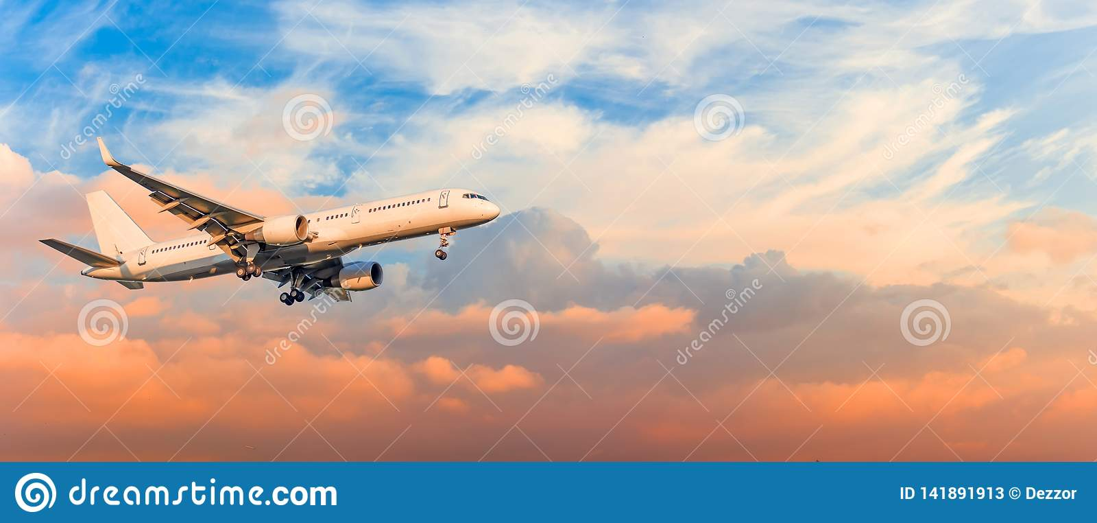 L avion de passager est vitesse d approche d atterrissage libérée, contre des nuages de ciel de coucher du soleil, panorama Aviat