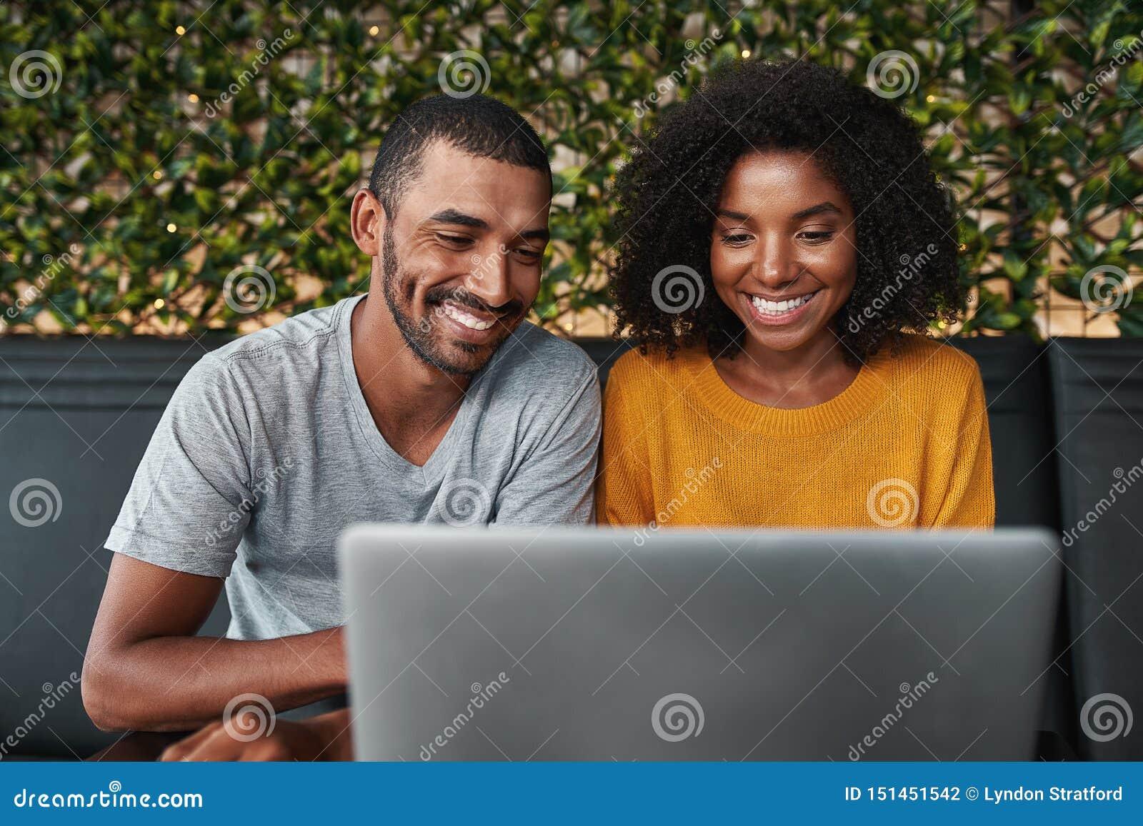 L?chelnde junge Paare unter Verwendung des Laptops