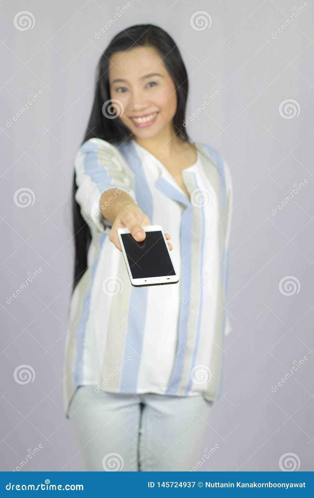 L?chelnder Frauenholdinghandy, geben Ihnen ein intelligentes Telefon Getrennt auf grauem Hintergrund