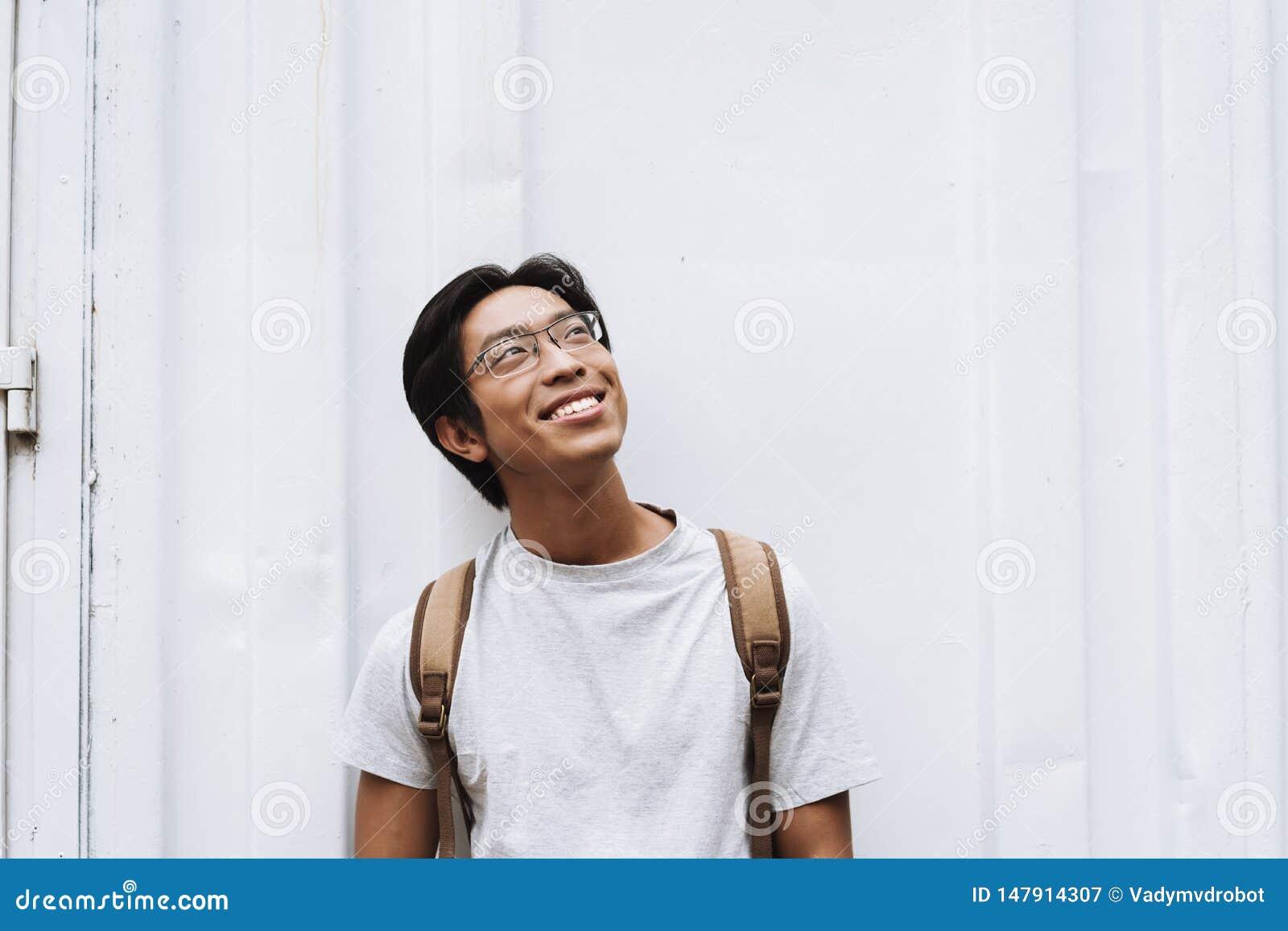 L?chelnder tragender Rucksack des jungen asiatischen Mannstudenten