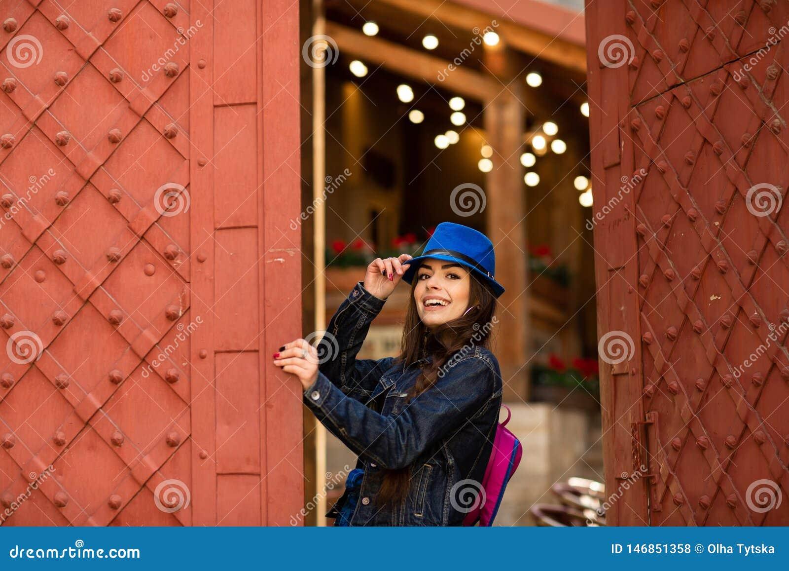 L?chelndes h?bsches M?dchen im blauen Hut nahe Altbau mit antiken roten T?ren Weibliche Baumusteraufstellung