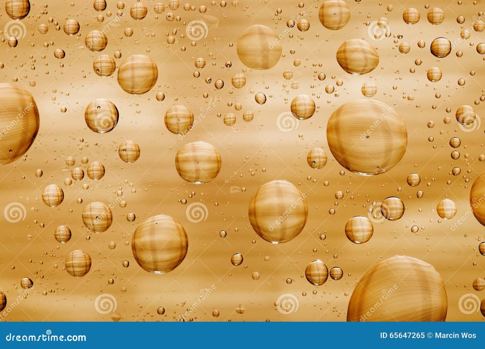 L eau laisse tomber le fond sur la surface d or Gouttelettes d eau sur des glas