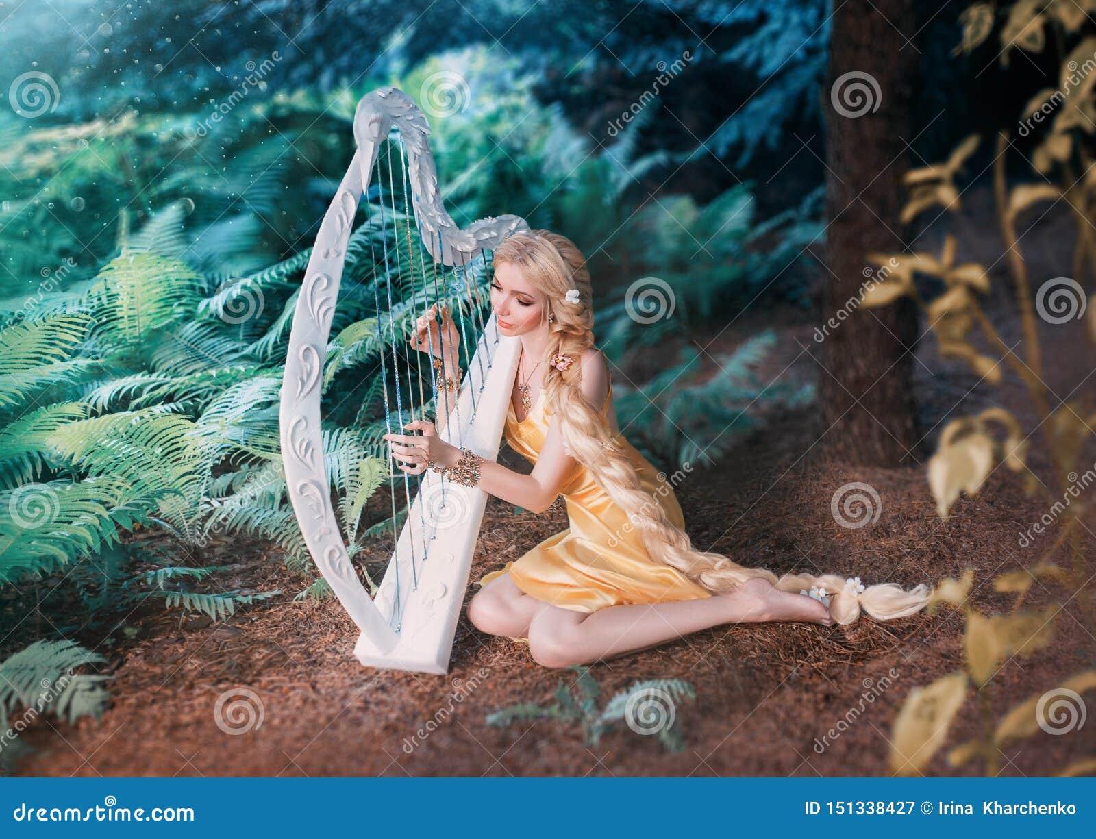 L elfo favoloso della foresta si siede nell ambito dell albero e dei giochi sull arpa bianca, ragazza con capelli biondi lunghi i