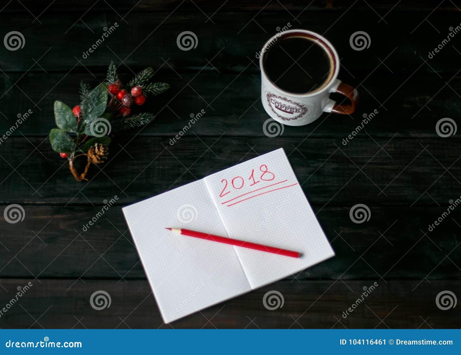 L Encore-vie avec un carnet avec une inscription rouge 2018, une tasse de café