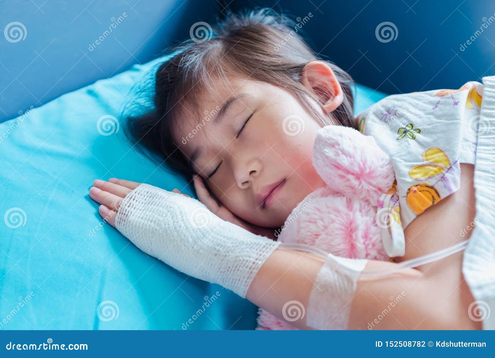 L enfant asiatique de maladie a admis dans l h?pital avec intraveineux salin en main