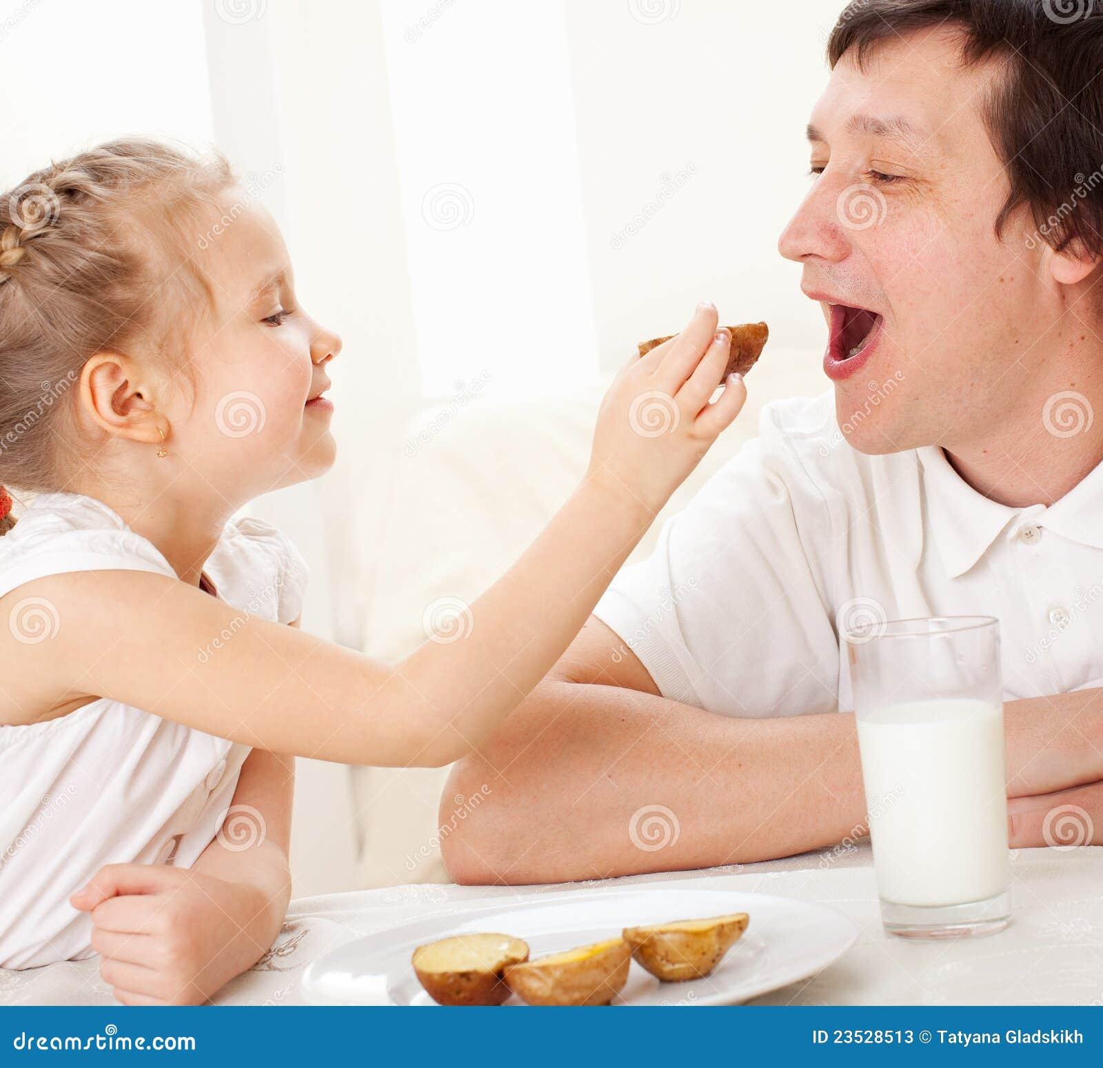 L enfant avec le père prennent un petit déjeuner