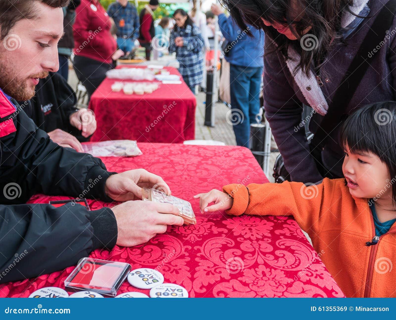 L enfant choisit le timbre de main du volontaire de jour de nourriture